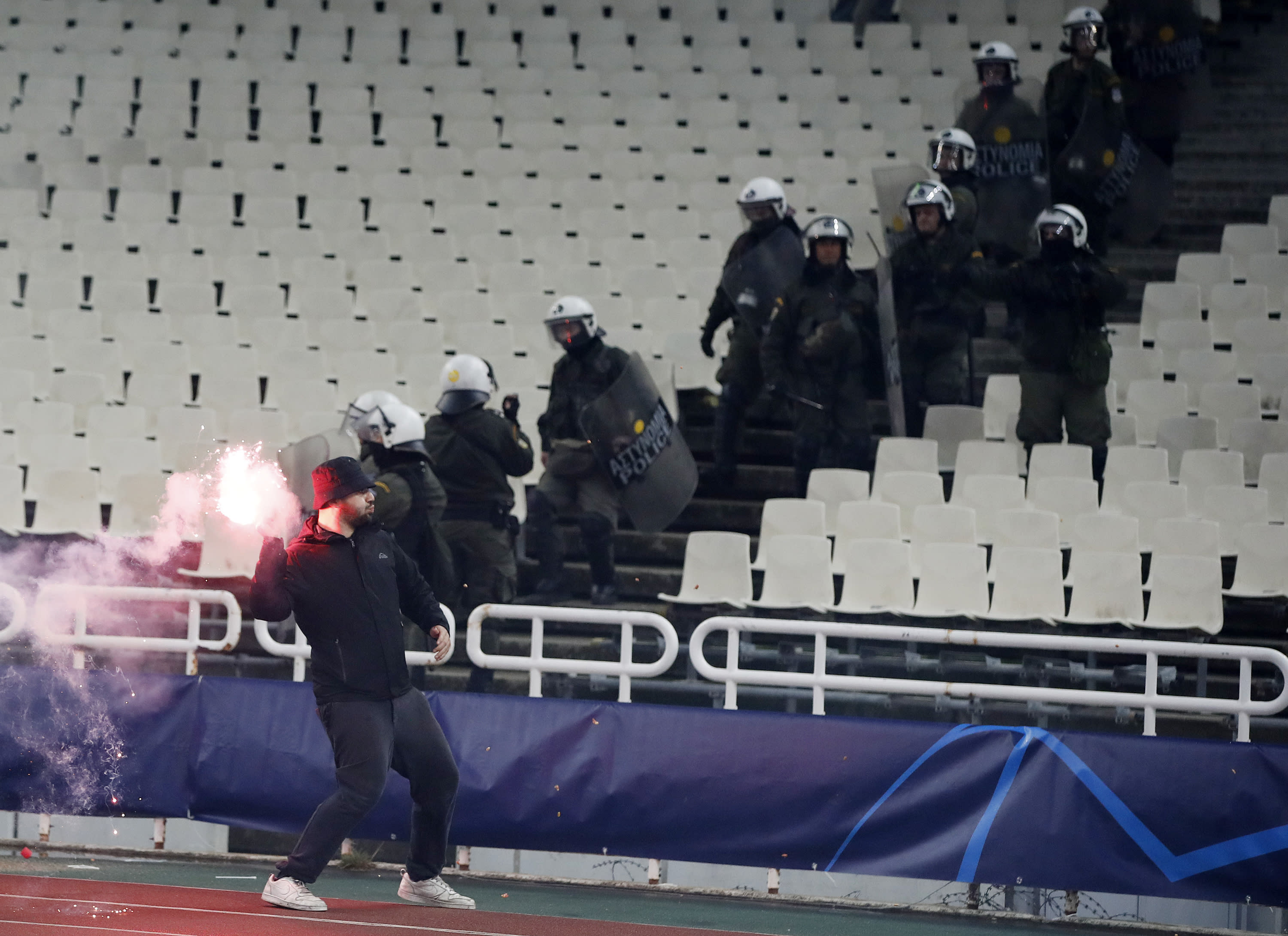 A fan throws a flare towards Ajax supporters during a Group E Champions League soccer match between AEK Athens and Ajax at the Olympic Stadium in Athens, Tuesday, Nov. 27, 2018. (AP Photo/Thanassis Stavrakis)