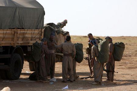 Kurdish peshmerga fighters prepare before leaving their base on the outskirts of Arbil in northern Iraq
