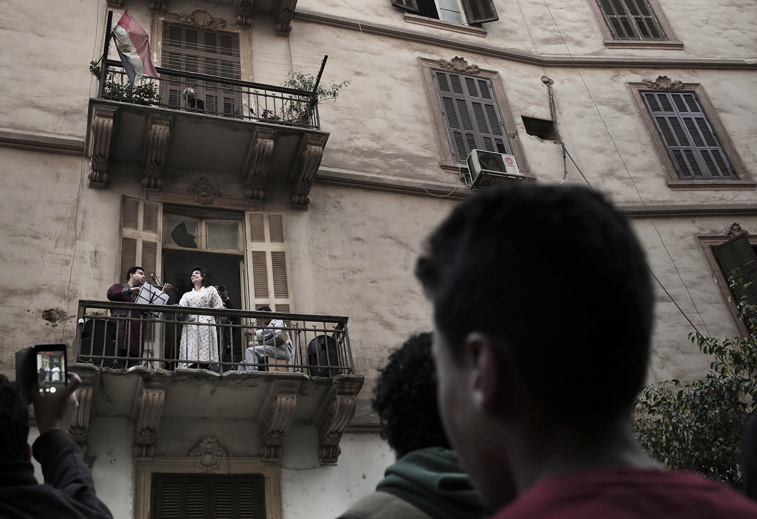 <p>An opera singer sings on a balcony, part of a performance tour by Mahatat for contemporary arts, in downtown Cairo, Egypt, Dec. 10, 2016. Mahatat for contemporary arts, a social and cultural enterprise based in Cairo, transforms public spaces to expose the arts in Egypt. (Photo: Nariman El-Mofty/AP) </p>