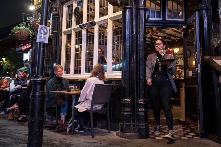 British pubs and bars were to start closing early after the government imposed new virus curbs