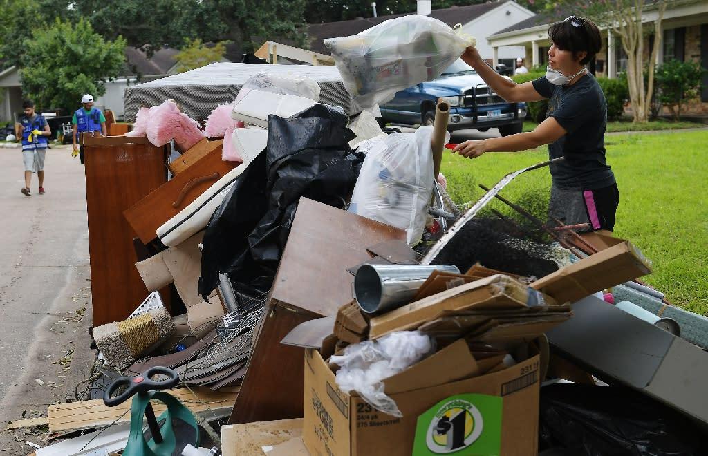 Kelsey Johnson tosses away a bag of flood-damaged belongings in front of her home in the Westbury neighborhood of southwest Houston (AFP Photo/MANDEL NGAN)