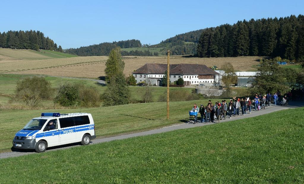A German police car escorts migrants walking from the Austrian-German border to the first registration point near the small Bavarian village of Wegscheid, on October 12, 2015
