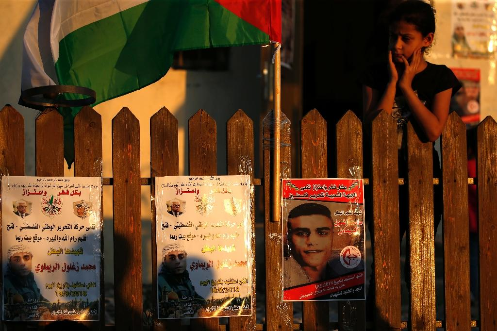 A neighbour of 24-year-old Palestinian Mohammed Khatib,died hours after being taken into custody during a raid in the early morning hours September 18, 2018, looks at his poster in the Beit Rima village, in the occupied West Bank later that day