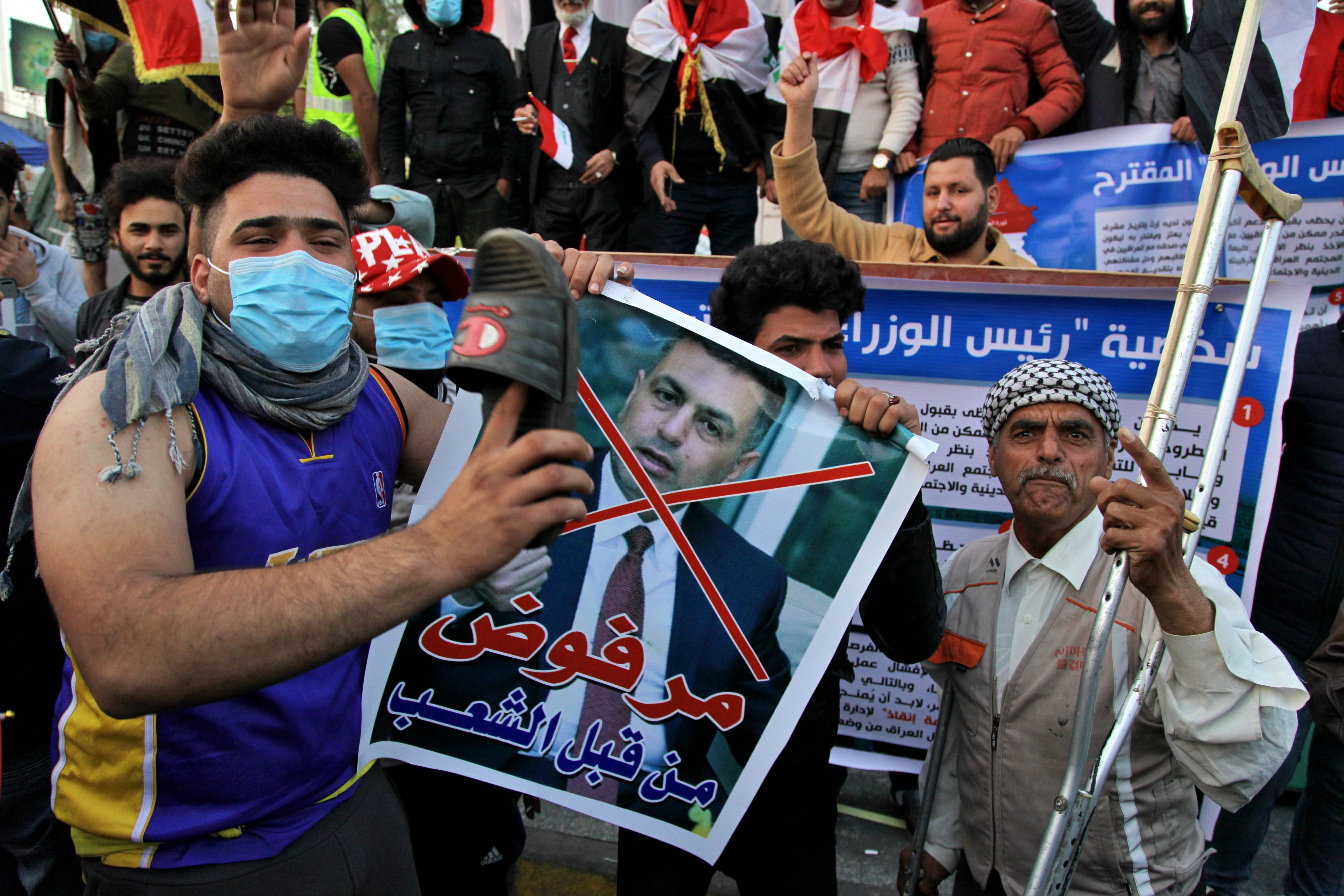 "A protester hits a poster with a defaced picture of Asaad al-Eidani, Iran-backed parliamentary bloc's nominee for the post of the prime minister and Arabic that reads ""rejected by the people,"" with a shoe during anti-government demonstrations in Baghdad, Iraq, Thursday, Dec. 26, 2019. Iraq's president refused Thursday to designate Asaad al-Eidani for the post of prime minister after he was rejected by anti-government protesters and said he was ready to submit his resignation to Parliament. (AP Photo/Khalid Mohammed)"