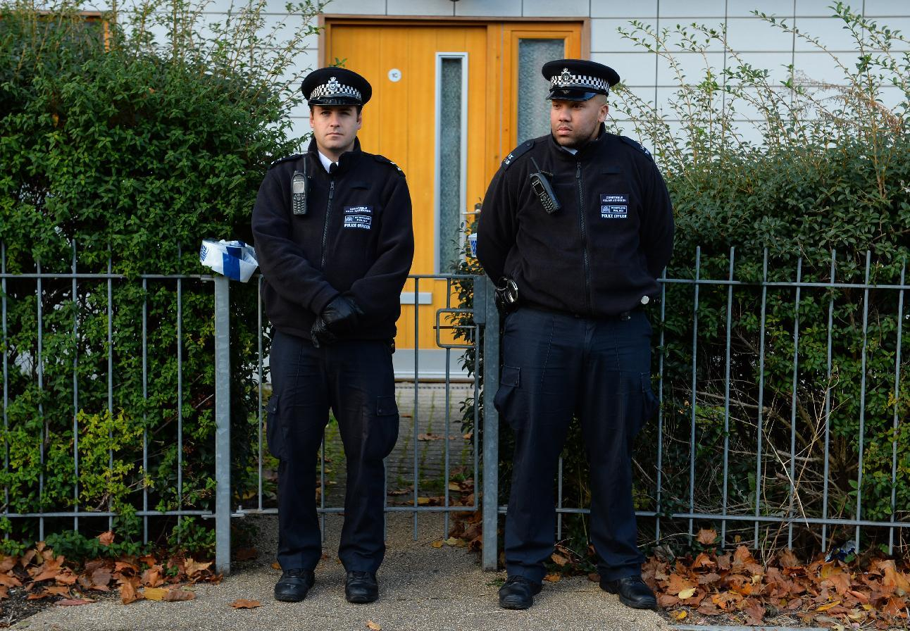 Police stand guard outside a block of residential flats in south London on November 23, 2013 after the recent discovery of three women held captive for 30 years (AFP Photo/Leon Neal)