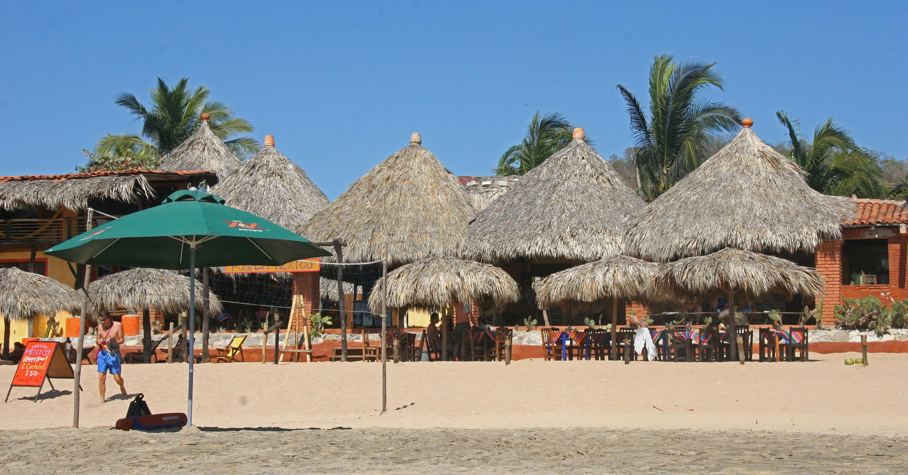 This Dec. 28, 2012 photo shows visitors relaxing at beachfront tables at the Posada Mexico restaurant in Zipolite, Mexico. A sleepy town with one main street and no ATMs, Zipolite is one many tiny coastal pueblos that dot the Pacific in Mexico's Southern state of Oaxaca. (AP Photo/Jody Kurash)