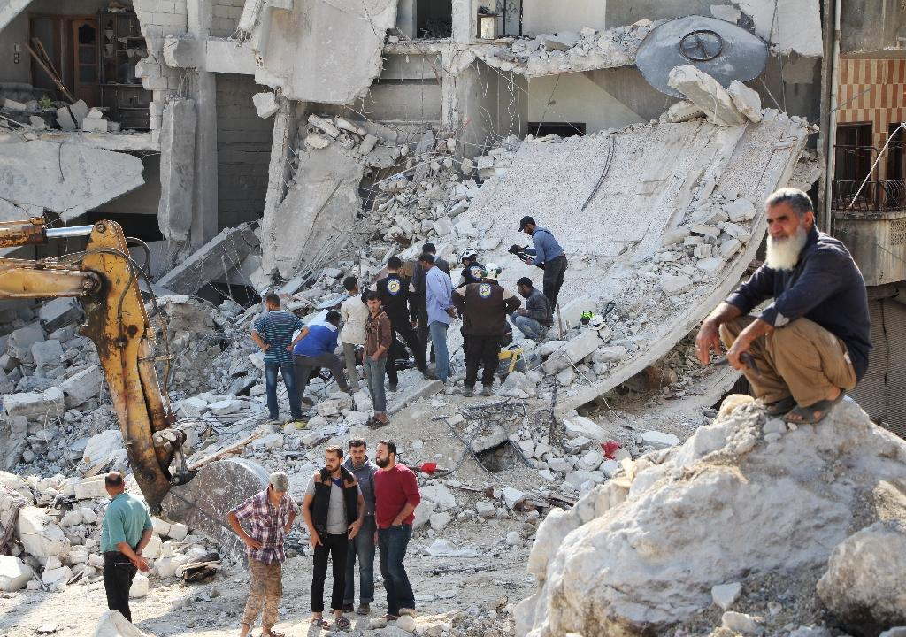 Syrian civil defence volunteers (C) search for victims amid the rubble of destroyed buildings on October 24, 2016, following overnight air strikes in the rebel-held town of Kafar Takharim, in Idlib province of northwest Syria (AFP Photo/Omar haj kadour)