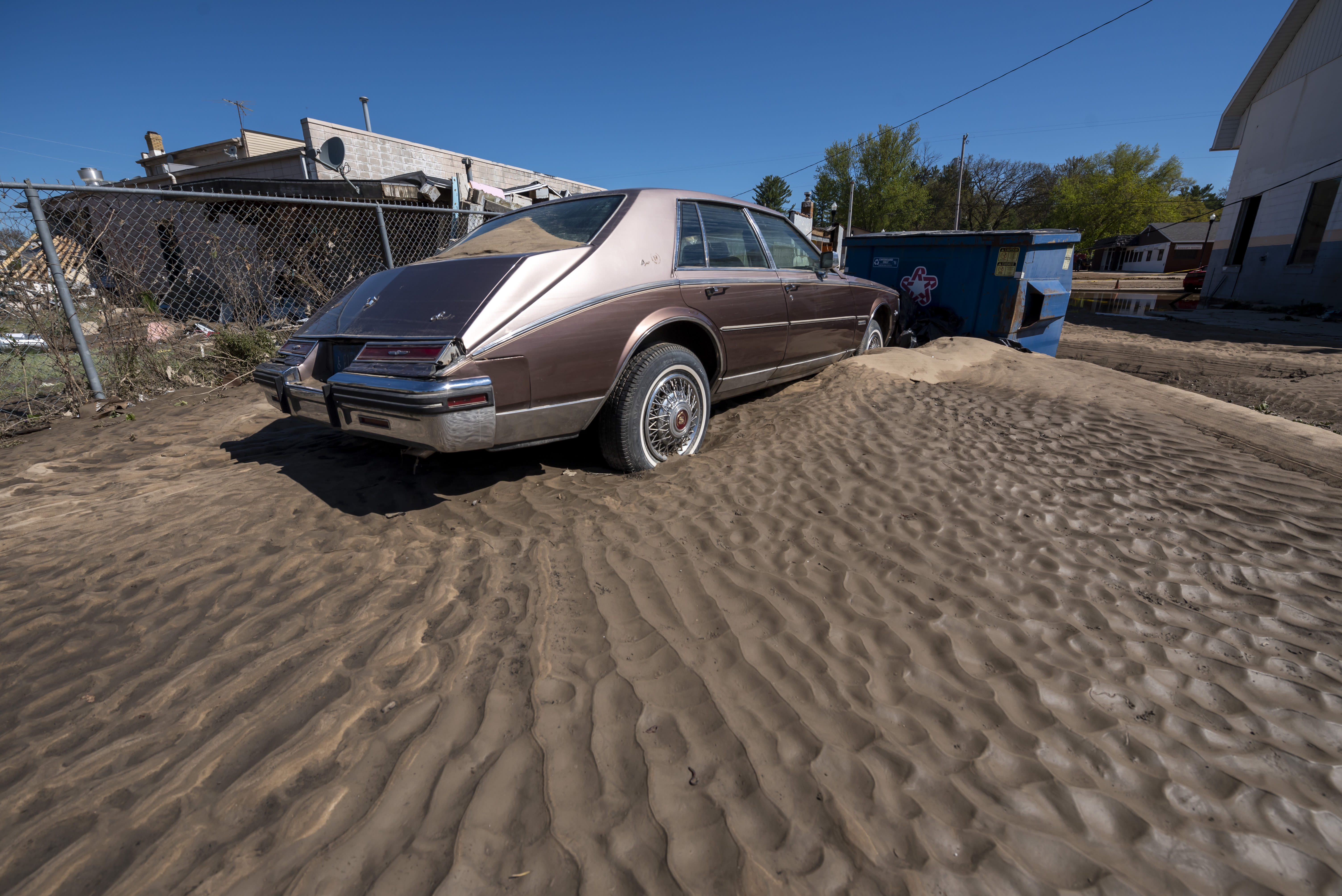 A Cadillac sits in a pile of sand as residents and business owners dig out after flooding swept through the town of Sanford, Thursday, May 21, 2020. Senior citizens are among the scores of displaced people staying in shelters after flooding overwhelmed two dams, submerged homes and washed out roads in Central Michigan. (David Guralnick/Detroit News via AP)