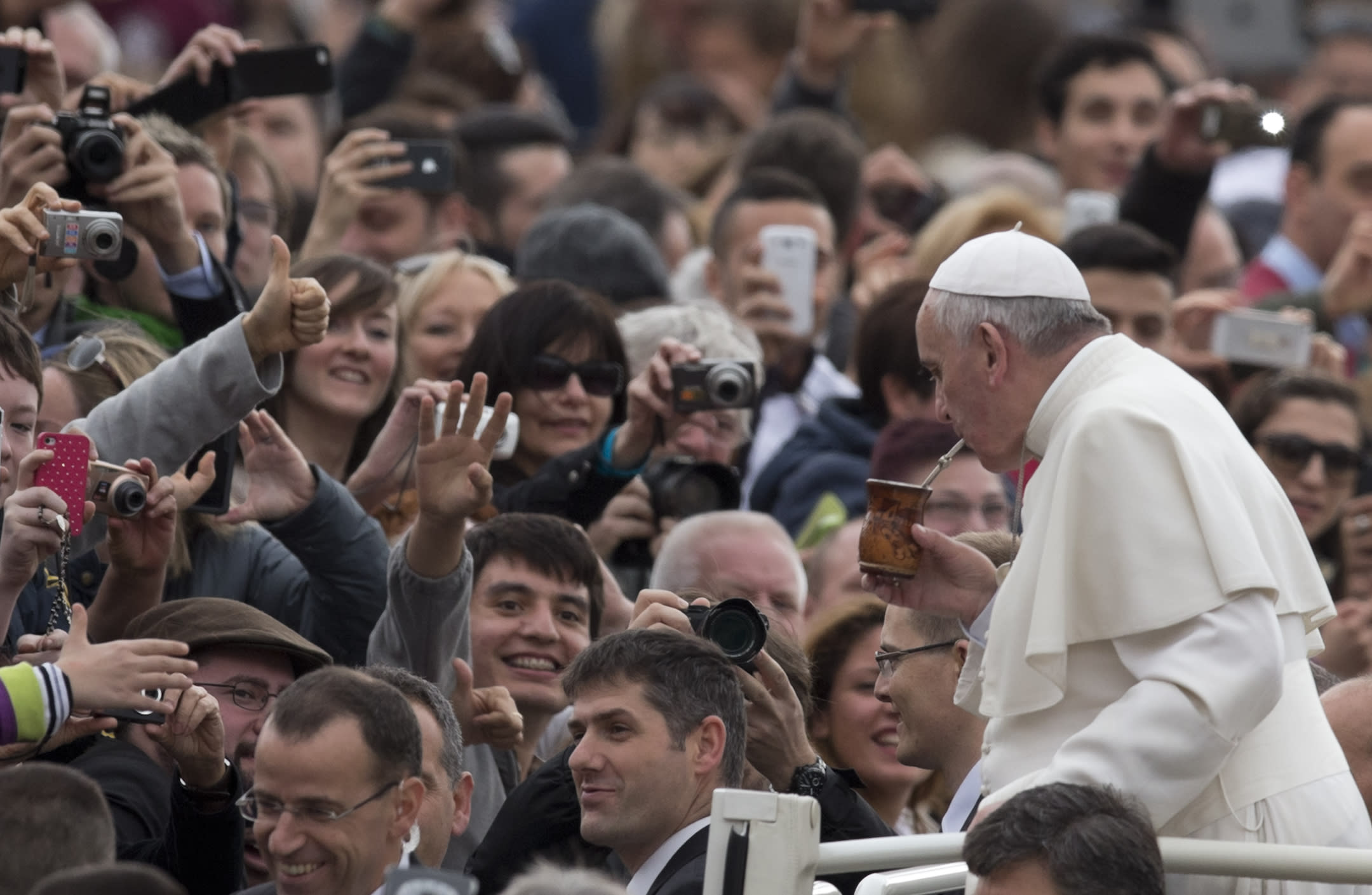 Pope Francis Pope drinks from a mate gourd, a traditional South American cup, we was offered as he is driven through the crowd in St. Peter's Square at the Vatican, prior to his general audience, Wednesday, Feb. 19, 2014. At public appearances, people offer Pope Francis gifts, and personal belongings to be blessed. (AP Photo/Alessandra Tarantino)