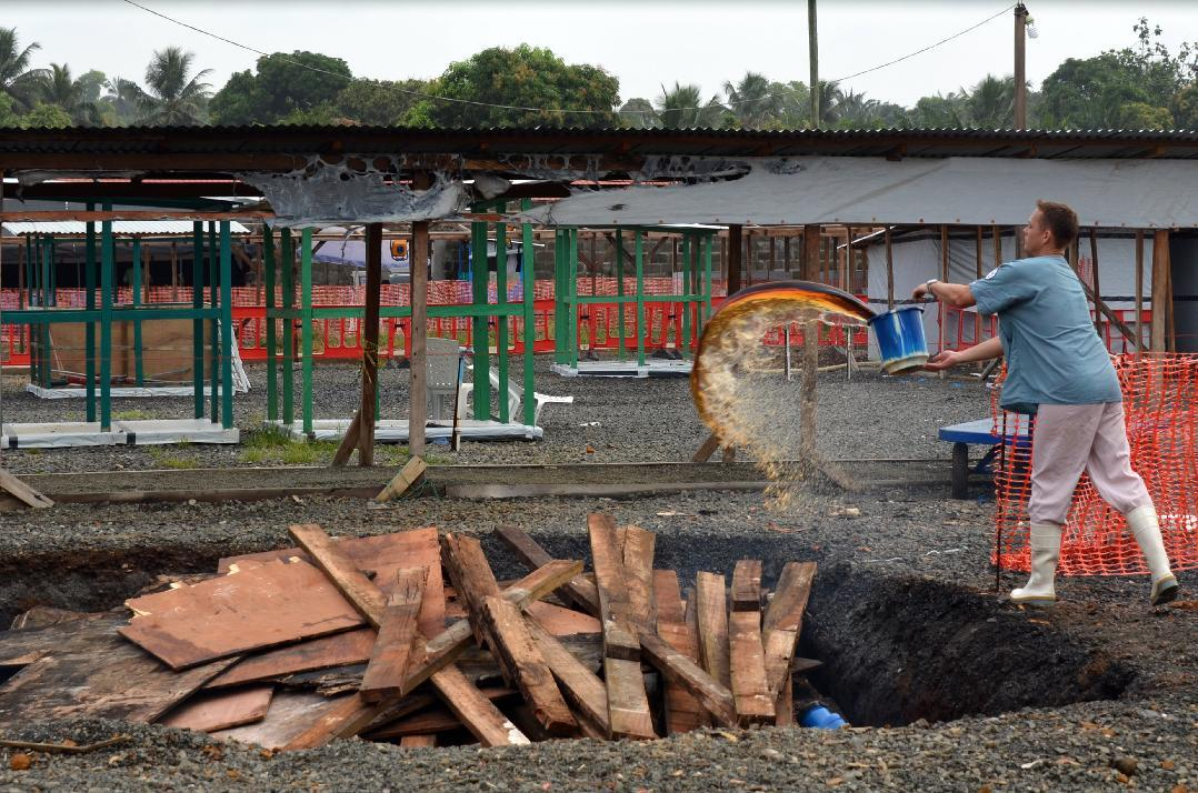 A Doctors Without Borders agent prepares to burn pieces of a dismantled tent on January 27, 2015 after the first section of the ELWA III Ebola Management Center in Monrovia was decomissioned (AFP Photo/Zoom Dosso)
