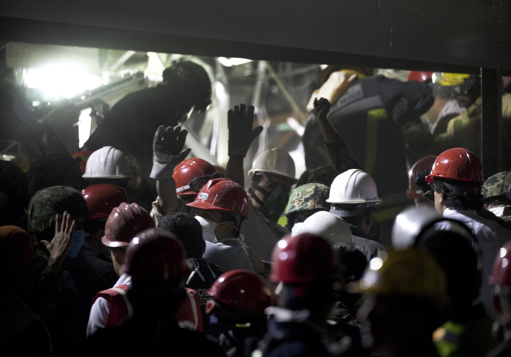 Rescue workers, firefighters and military search for survivors at the site of an explosion in a building at Mexico's state-owned oil company PEMEX complex, in Mexico City, Thursday Jan. 31, 2013. The explosion killed more than 10 people and injured some 80 as it heavily damaged three floors of the building. According to civil protection and local media some people remained trapped in the debris from the explosion, which occurred in the basement of an administrative building next to the iconic, 52-story tower of Petroleos Mexicanos, or PEMEX. (AP Photo/Eduardo Verdugo)