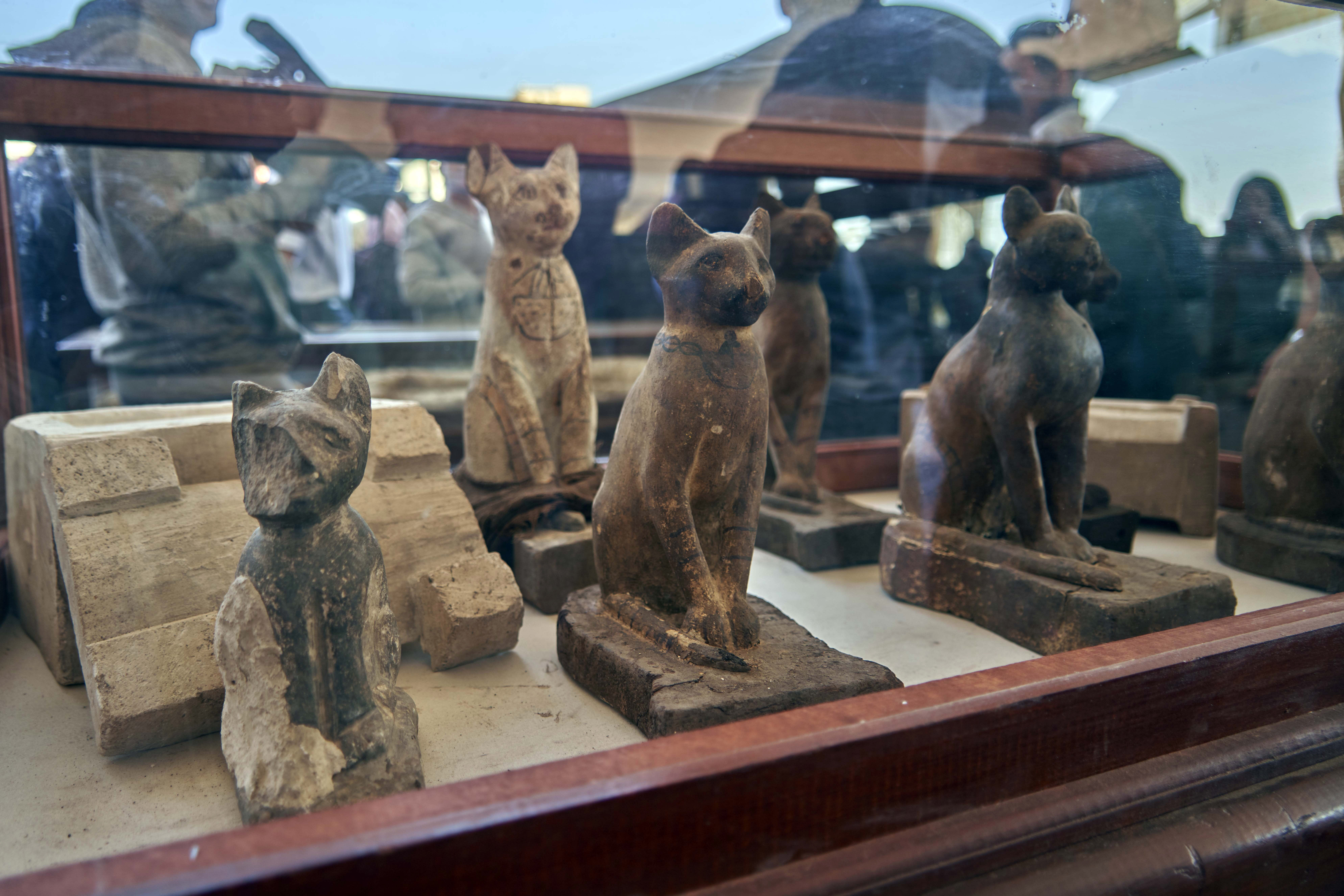 An extensive collection of 75 wooden and bronze statues of cats of different shapes and sizes are displayed in Saqqara, south Giza, Egypt. Saturday, Nov. 23, 2019. Egypt's Ministry of Antiquities revealed details on recently discovered animal mummies, saying they include two lion cubs as well as several crocodiles, birds and cats. The new discovery was displayed at a makeshift exhibition at the famed Step Pyramid of Djoser in Saqqara, south of Cairo, near the mummies and other artifacts were found in a vast necropolis. (AP Photo/Hamada Elrasam)