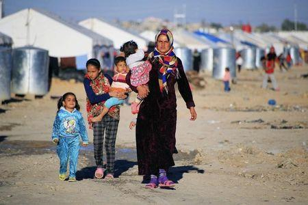Civilians who fled from Diyala province walk at refugee camp in Khanaqin city, February 6, 2015. REUTERS/Ahmad Mousa