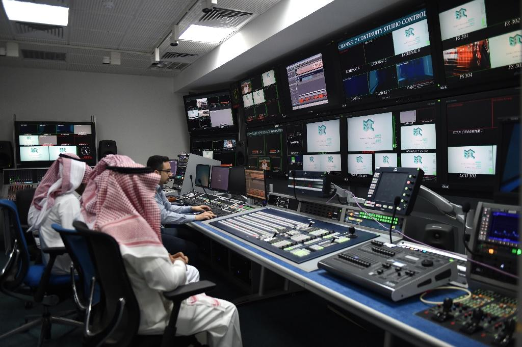 An employee works with trainees at SBC, a new channel under the umbrella of the Saudi Broadcasting Corporation in Riyadh, on April 24, 2018. (AFP Photo/FAYEZ NURELDINE)