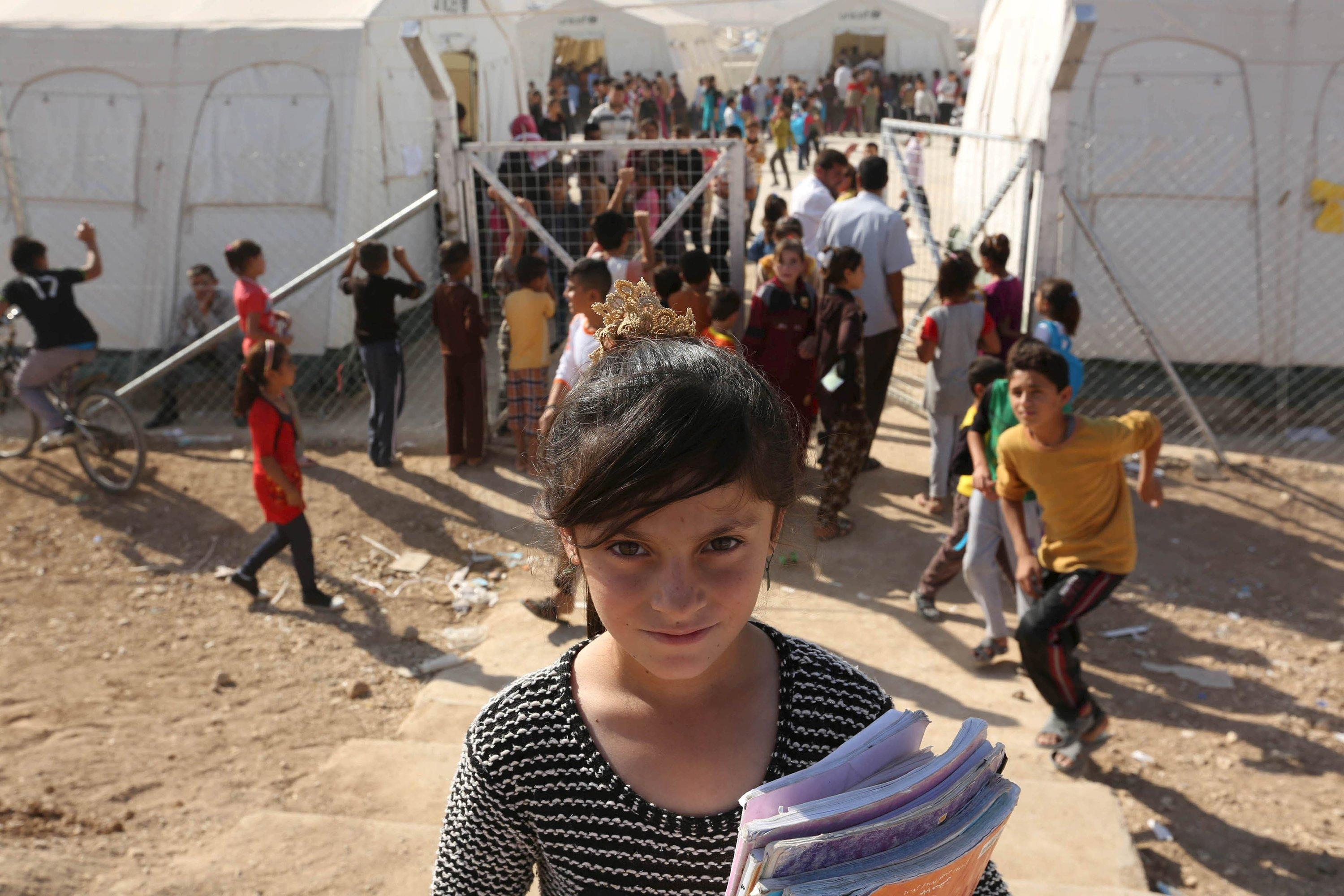 A Yazidi refugee girl from the minority Yazidi sect poses for a photograph on the first day of the new school term at Sharya refugee camp, on the outskirts of Duhok province, October 17, 2015. REUTERS/Ari JalaFOR EDITORIAL USE ONLY. NO RESALES. NO ARCHIVE.