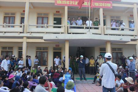 Catholic Priest Anthony Dang Huu Nam (C) talks with Vietnamese fishermen waiting outside the people's court as they prepare to sue Formosa Ha Tinh Steel, a subsidiary of Taiwan's Formosa Plastics, over an accident at one of its steel plant which caused massive fish deaths along a 200km (120 mile) stretch of coastline, in Vietnam's central province of Ha Tinh, September 26, 2016. Handout via REUTERS