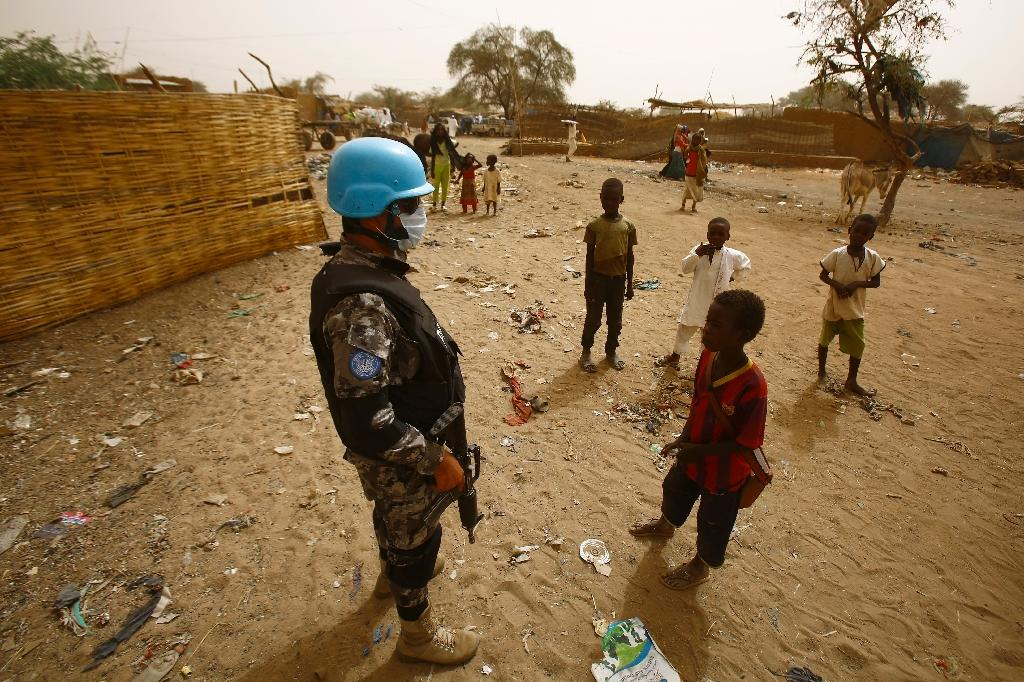 Sudanese children stand next to a member of the UN-Afrcian Union mission in Darfur (UNAMID), a mission that expects significant troop cuts under a proposal for strategic review