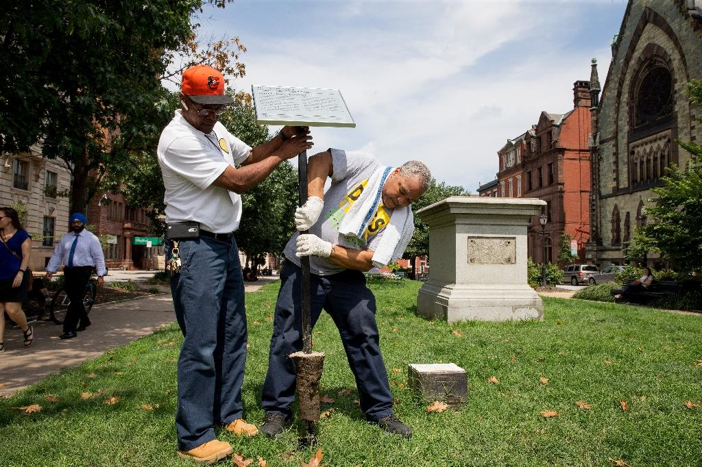 City workers remove the detail sign at the former Roger B. Taney monument in Mount Vernon Place in Baltimore, Maryland, after it was removed by the city on August 16, 2017 (AFP Photo/TASOS KATOPODIS)