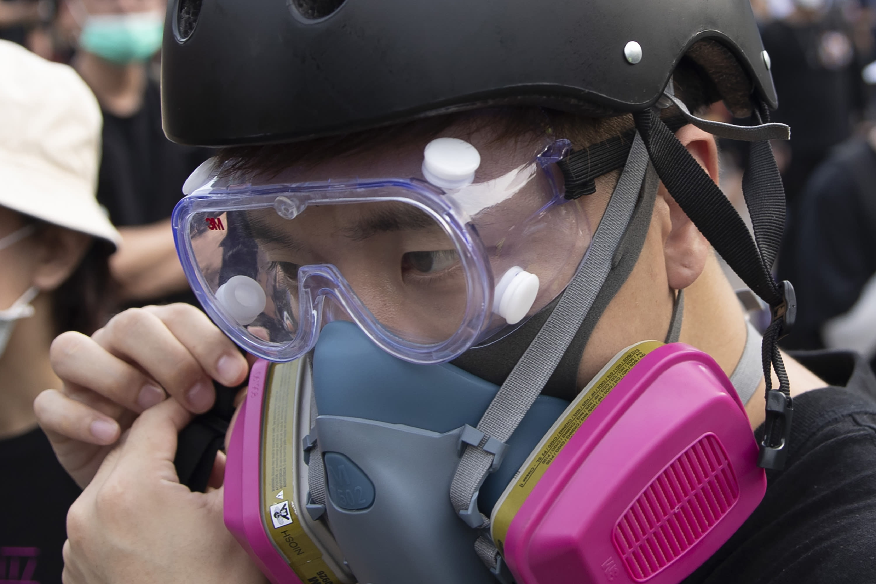 "In this Aug. 16, 2019, photo, Wayne, a 33-year-old self-described ""front line"" protester, adjusts his gas mask stands along with other demonstrators in Tai Po, on Hong Kong's outskirts. Hong Kong's protest movement has reached a moment of reckoning after protesters occupying the airport held two mainland Chinese men captive, and pro-democracy lawmakers and fellow demonstrators question whether the whole operation has gone too far. (AP Photo/Vincent Thian)"