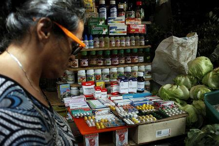 A woman walks past a fruit and vegetables stall selling medicines at a market in Rubio, Venezuela December 5, 2017. REUTERS/Carlos Eduardo Ramirez