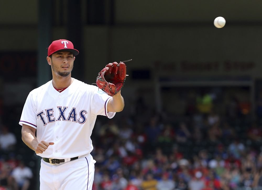 Texas Rangers starting pitcher Yu Darvish gets the ball returned to him as he works the first inning of a baseball game against the Los Angeles Angels in Arlington, Texas, Sunday, July 9, 2017