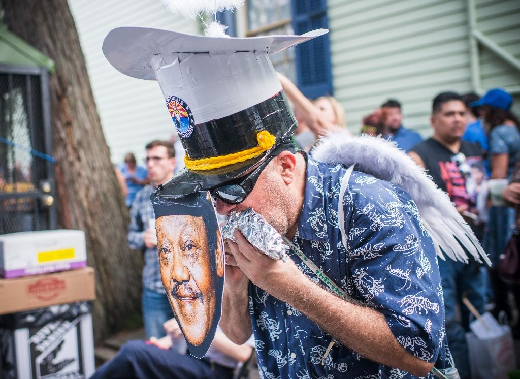 A man enjoys a hot dog behind a Fats Domino mask during the Second Line for the late US musician in the 9th Ward of New Orleans, Louisiana (AFP Photo/Emily KASK)