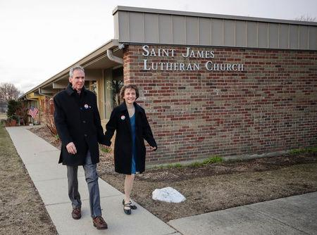 U.S. Congressman Daniel Lipinski walks with wife Judy Lipinski after voting  in the Democratic Party's congressional