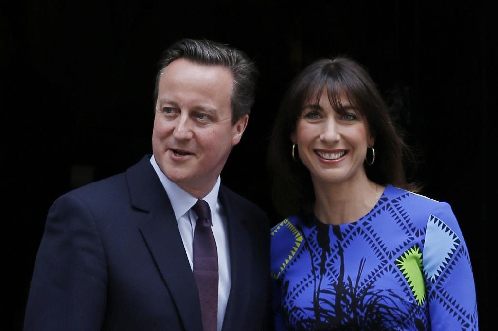 Britain's Prime Minister and Leader of the Conservative Party David Cameron (L) and his wife Samantha pose for pictures outside 10 Downing Street in London on May 8, 2015, a day after the British general election (AFP Photo/Adrian Dennis)
