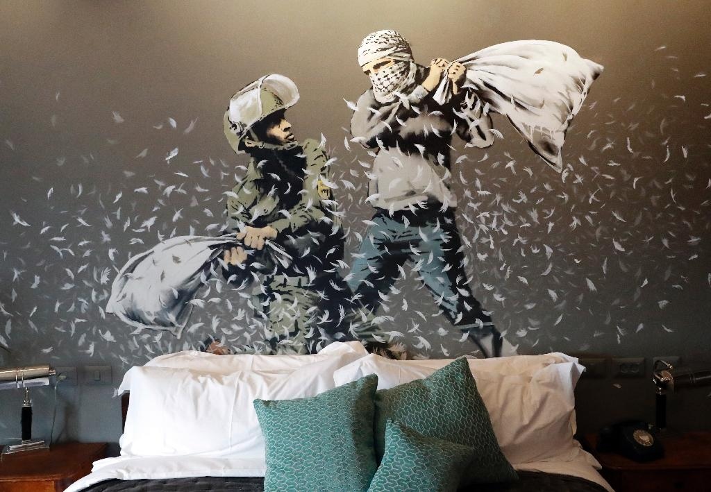 An Israeli soldier and Palestinian protester fight with pillows in one room of British street artist Banky's hotel in Bethlehem (AFP Photo/THOMAS COEX)
