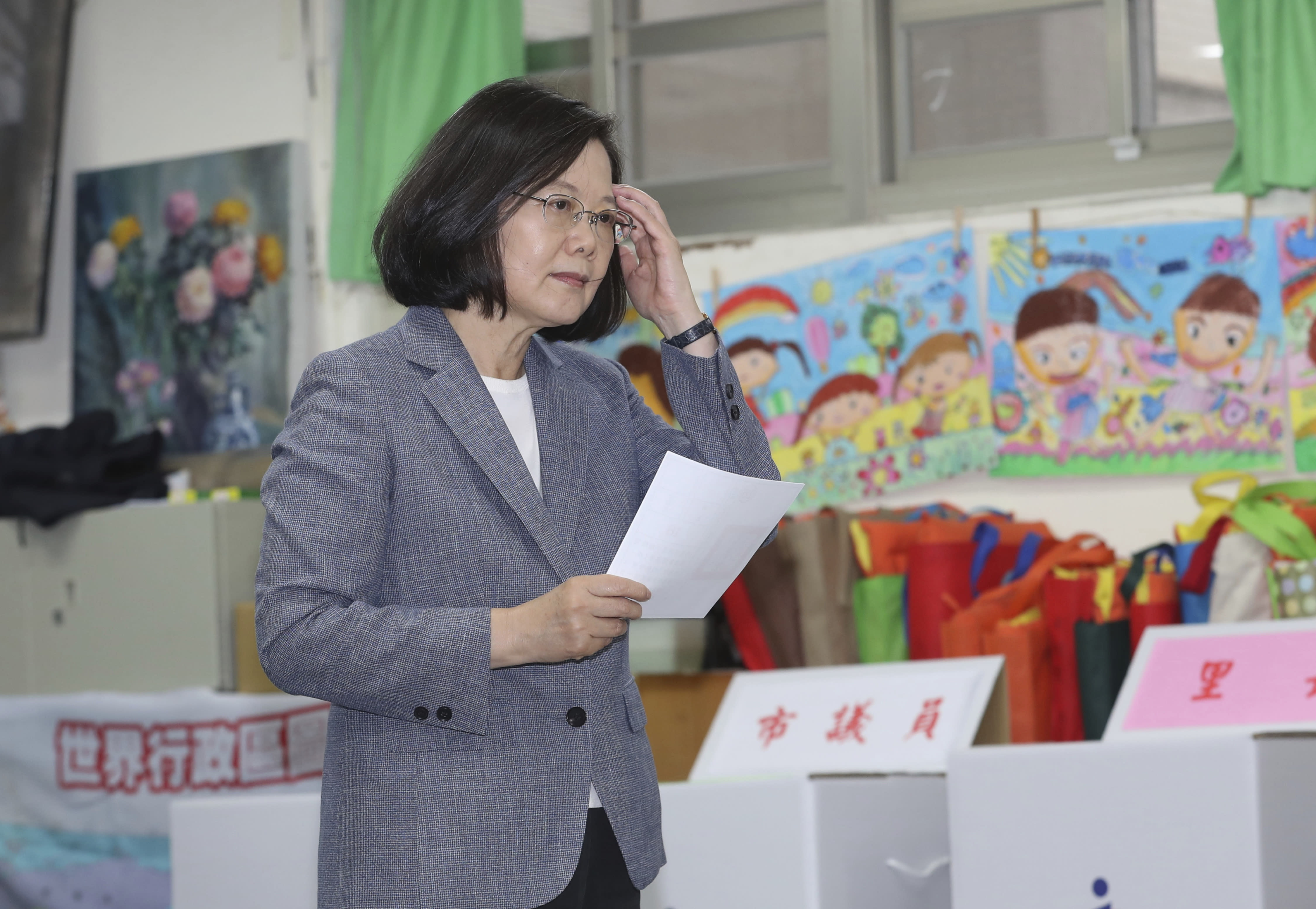 Taiwanese President Tsai Ing-wen waits to cast her ballot at a polling station, Saturday, Nov. 24, 2018, in Taipei, Taiwan. Taiwanese began voting in midterm local elections Saturday seen as a referendum on the independence-leaning administration of President Tsai, amid growing pressure from the island's powerful rival China. (Chang Haoan/ Pool Photo via AP)