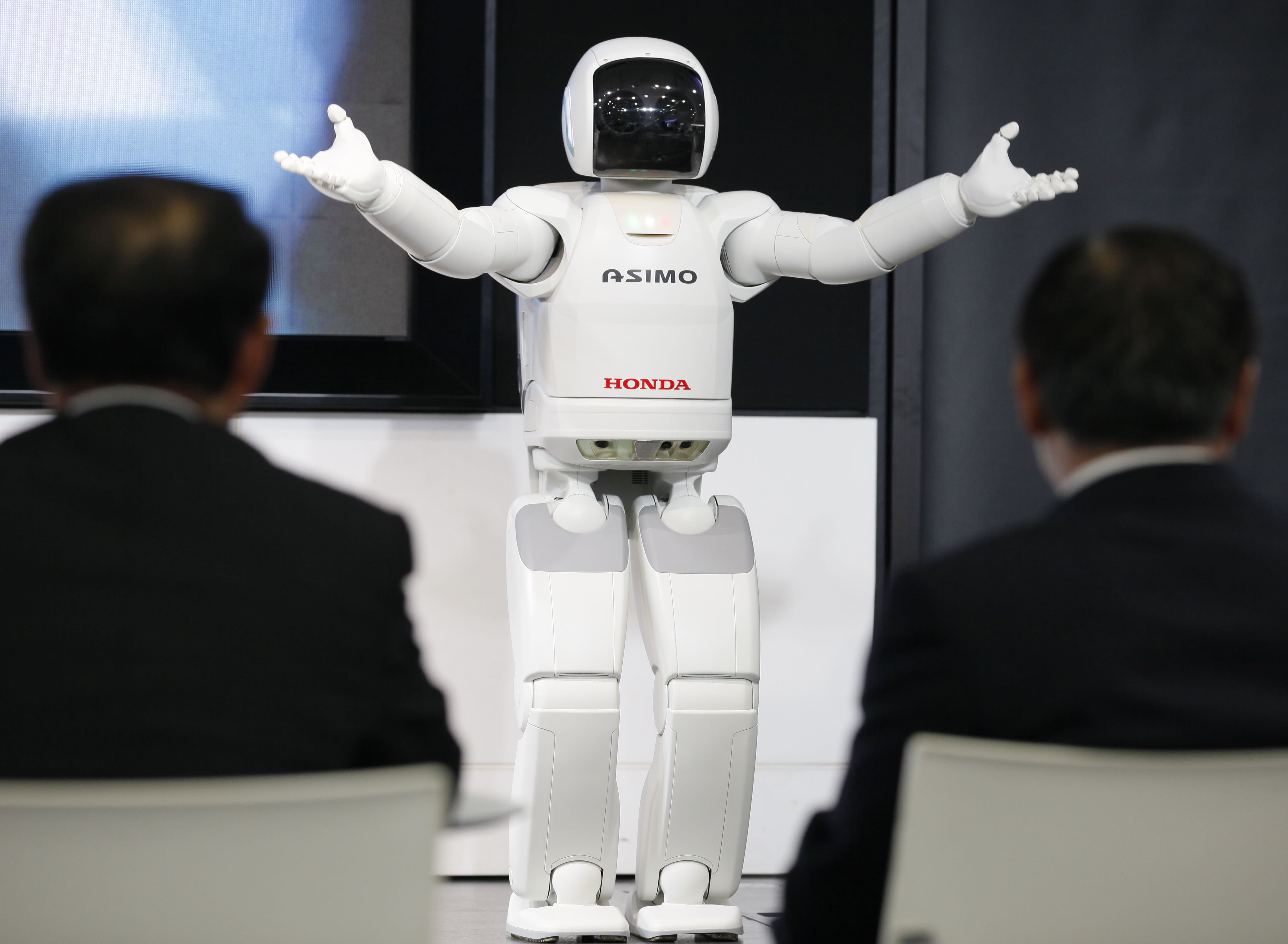 FILE - In this April 27, 2012 file photo, visitors watch a Honda Asimo robot performing at a showroom at the headquarters of Honda Motor Co. in Tokyo. Canon Inc. is moving toward fully automating digital camera production in an effort to cut costs - a key change being played out across Japan, a world leader in robotics. If successful, counting on machines can help preserve this nation's technological power - not the stereotype of machines snatching assembly line jobs from workers, Jun Misumi - company spokesman, said Monday, May 14. (AP Photo/Koji Sasahara, File)