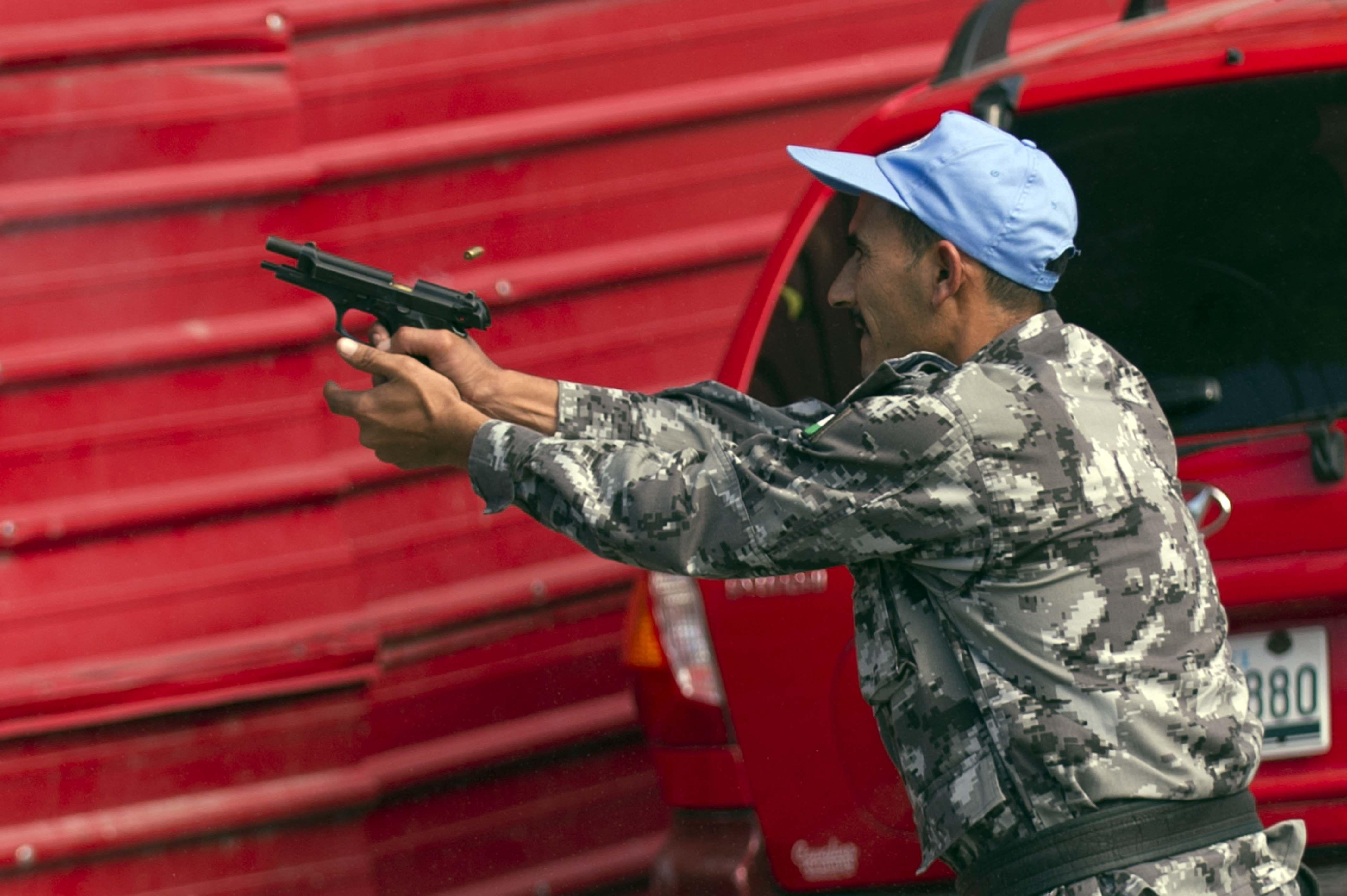 A member of the United Nations Stabilization Mission in Haiti (MINUSTAH) fires his gun against demonstrators during clashes in a protest against the government of President Michel Martelly in Port-au-Prince, on December 12, 2014