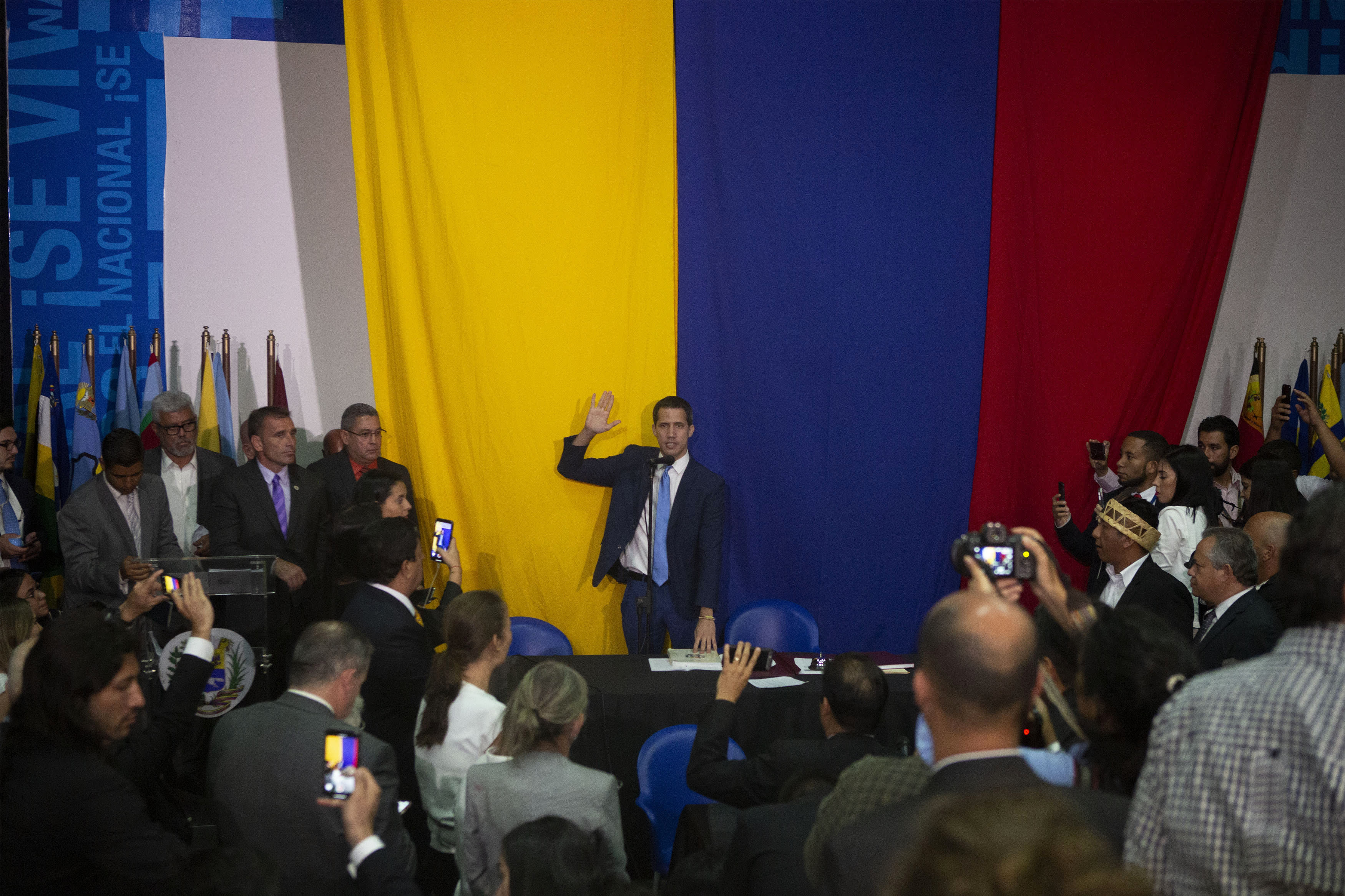 National Assembly President Juan Guaido swears himself in as President of the National Assembly with opposition lawmaker votes at the newspaper El Nacional's headquarters in Caracas, Venezuela, Sunday, Jan. 5, 2020. (AP Photo/Andrea Hernandez Briceño)