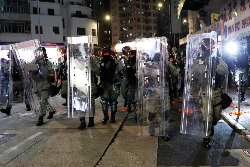 Riot police officers make their way along the street trying to disperse protesters gathering for a demonstration in Hong Kong