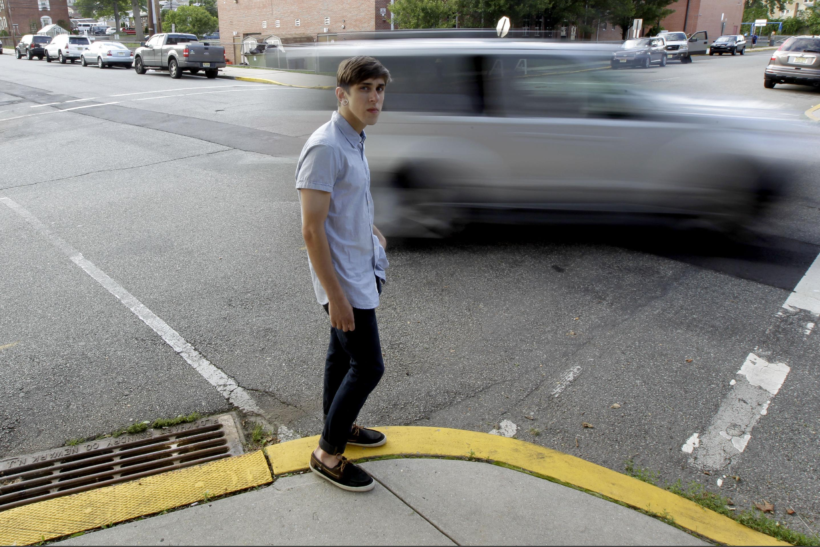Dylan Young, 18, poses for The Associated Press as a vehicle cruises by, Wednesday, June 6, 2012, in North Arlington, N.J. Young, a senior at North Arlington High, was in a fender-bender accident caused by being distracted while texting and driving. More than half of high school seniors say they text or email while driving, according to a jarring new study that offers the first federal statistics on how common the dangerous habit is in teens. The Centers for Disease Control and Prevention released the numbers Thursday, June 7, 2012. They come from a 2011 survey of about 15,000 high school students across the country. The study found 58 percent of high school seniors said that, in the previous month, they had texted or emailed while driving. (AP Photo/Julio Cortez)