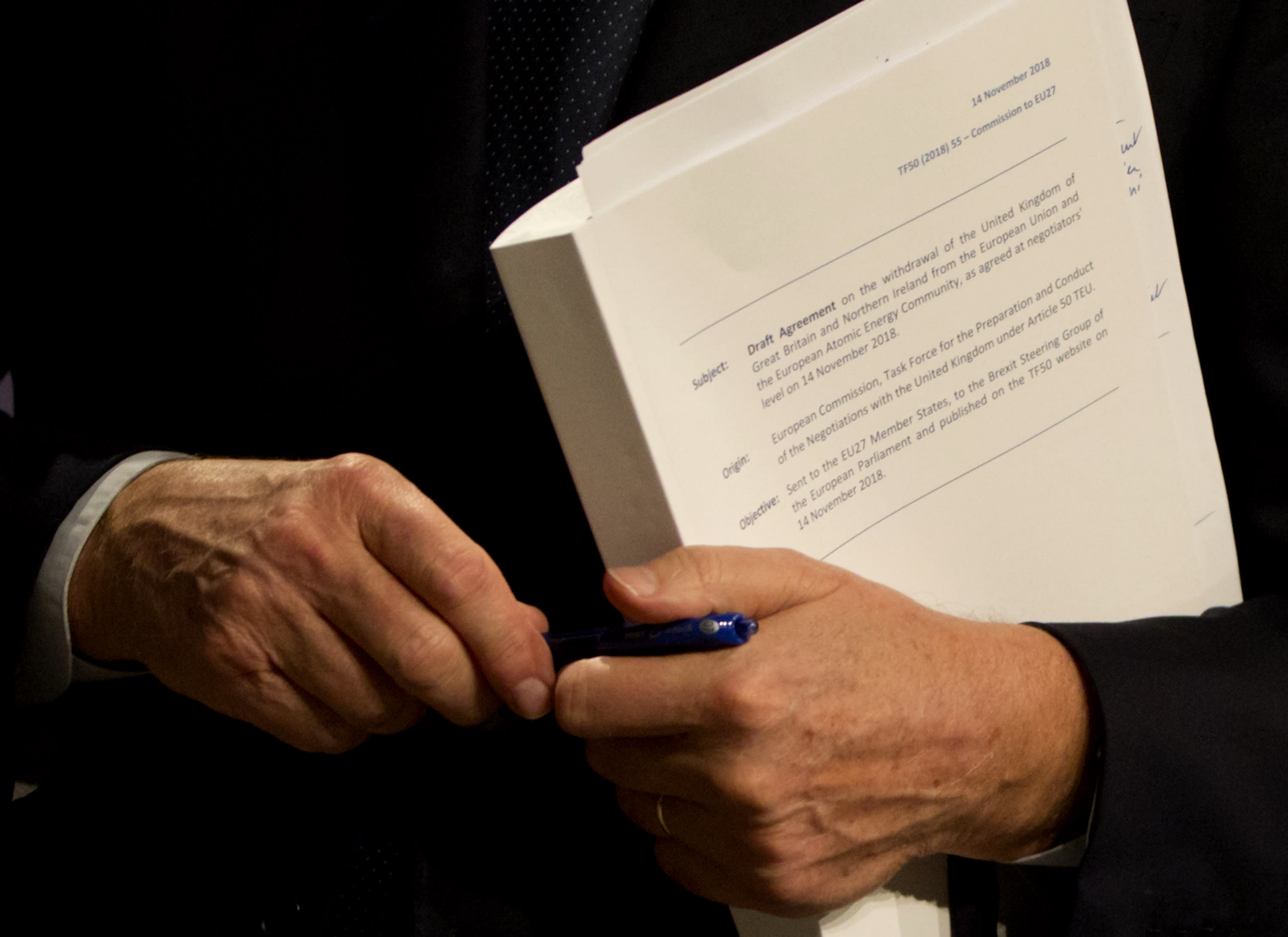 EU chief Brexit negotiator Michel Barnier holds the draft withdrawal agreement during a media conference in Brussels on Wednesday, Nov. 14, 2018. EU ambassadors met in Brussels Wednesday, in a closed door session, to discuss the draft agreement. (AP Photo/Virginia Mayo)