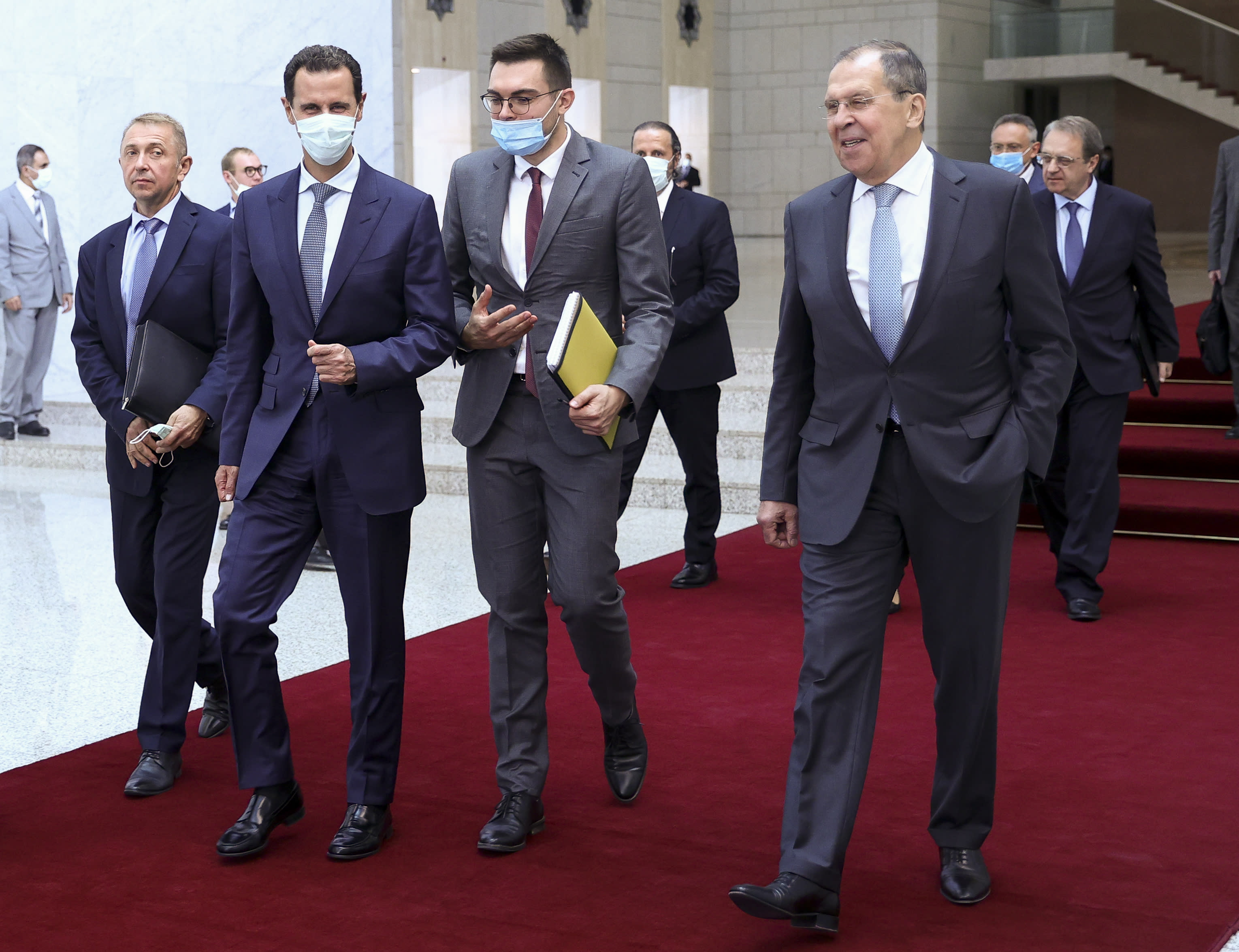 In this photo released by Russian Foreign Ministry Press Service, Russian Foreign Minister Sergey Lavrov, right, and Syrian President Bashar al-Assad, second left, walk after their talks in Damascus, Syria, Monday, Sept. 7, 2020. Russia's foreign minister has met with Syrian President Bashar Assad shortly after landing in the Syrian capital on his first visit since 2012. Russia has been a close ally of Assad in Syria's long and bloody nine-year-long civil war, lending his government in Damascus vital military, economic and political support. (Russian Foreign Ministry Press Service via AP)
