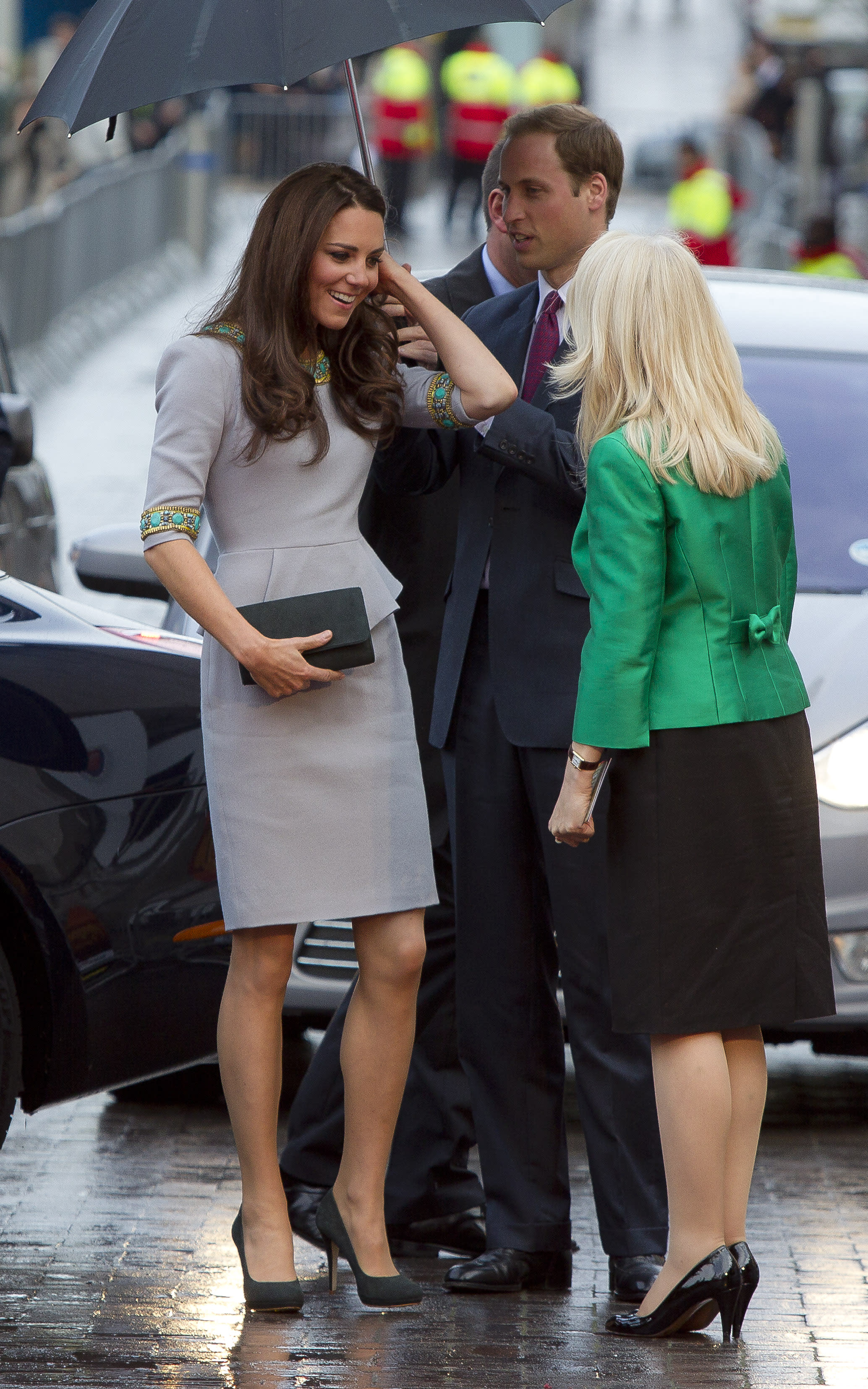 The Duchess of Cambridge is greeted as she arrives under an umbrella for the UK Premiere of 'African Cats', in aid of Tusk Trust, at the BFI Southbank in central London, Wednesday, April 25, 2012. (AP Photo/Joel Ryan)