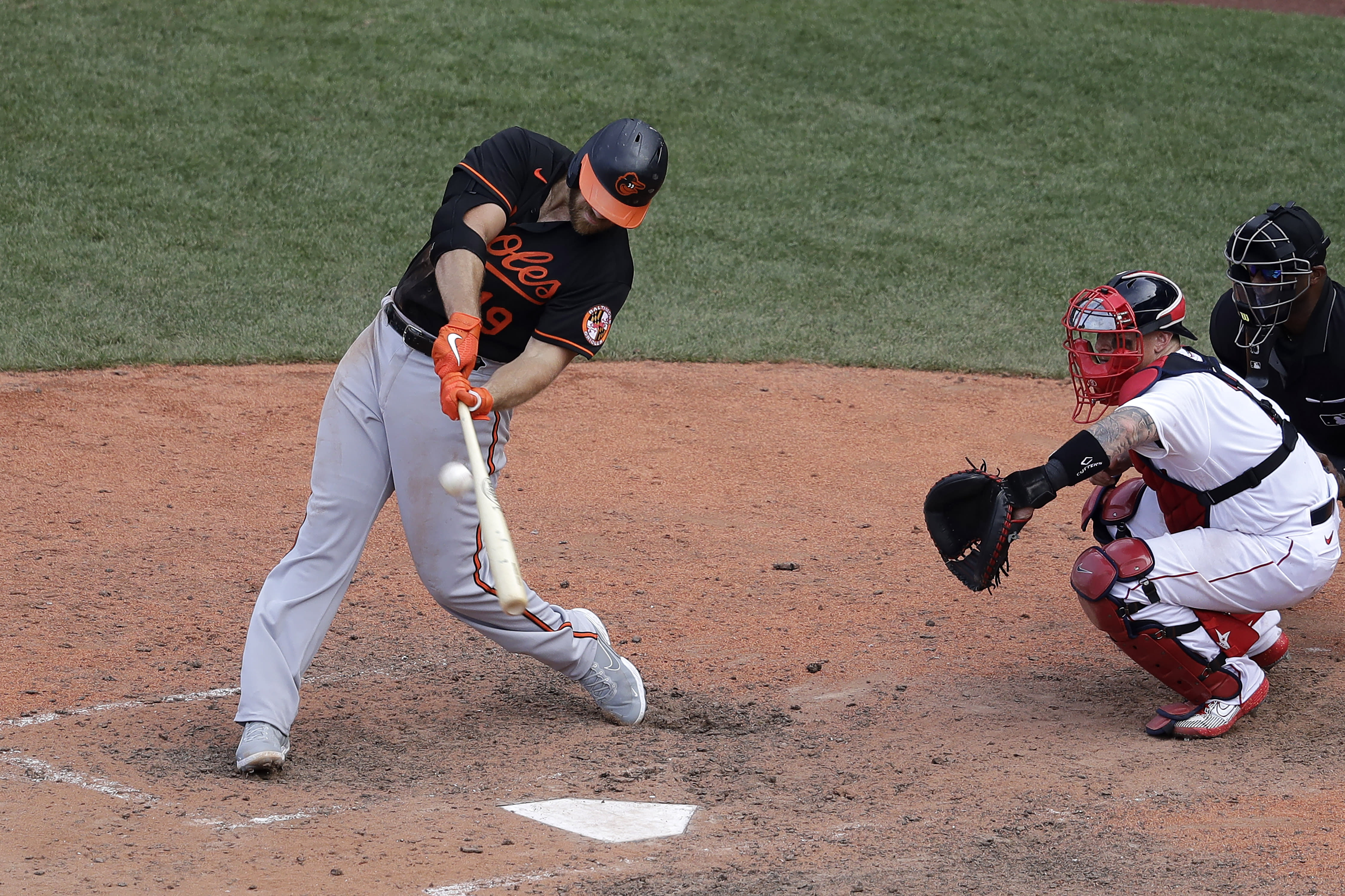 Baltimore Orioles' Chris Davis, left, hits an RBI-double as Boston Red Sox's Christian Vazquez looks on during the ninth inning of a baseball game, Sunday, July 26, 2020, in Boston. (AP Photo/Steven Senne)