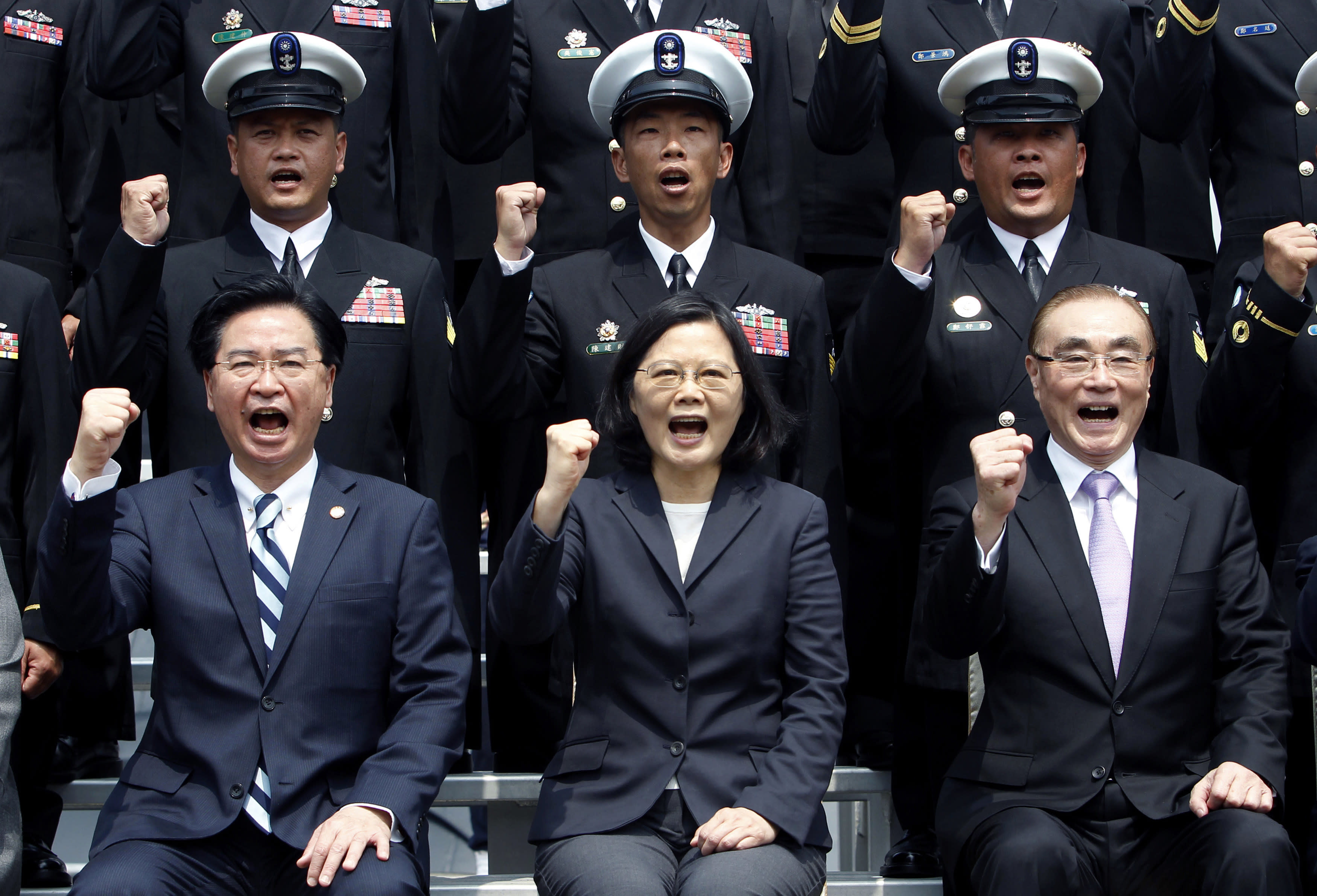 """FILE - In this March 21, 2017, file photo, Taiwan's President Tsai Ing-wen, center, along with Defense Minister Feng Shih-kuan, right, and Secretary-General of National Security Council Joseph Wu, left, cheer with navy officers during a visit to Zuoying Naval base in Kaohsiung, southern Taiwan. China says attempts by Taiwan's government to block its goal of bringing the self-governing island under Beijing's control are like """"stretching out an arm to block a car."""" The new rhetorical broadside was launched late Tuesday, March 12, 2019 against Taiwanese President Tsai following her announcement of guidelines to counter China's """"one country, two systems"""" framework for political unification with the island. (AP Photo/Chiang Ying-ying, File)"""