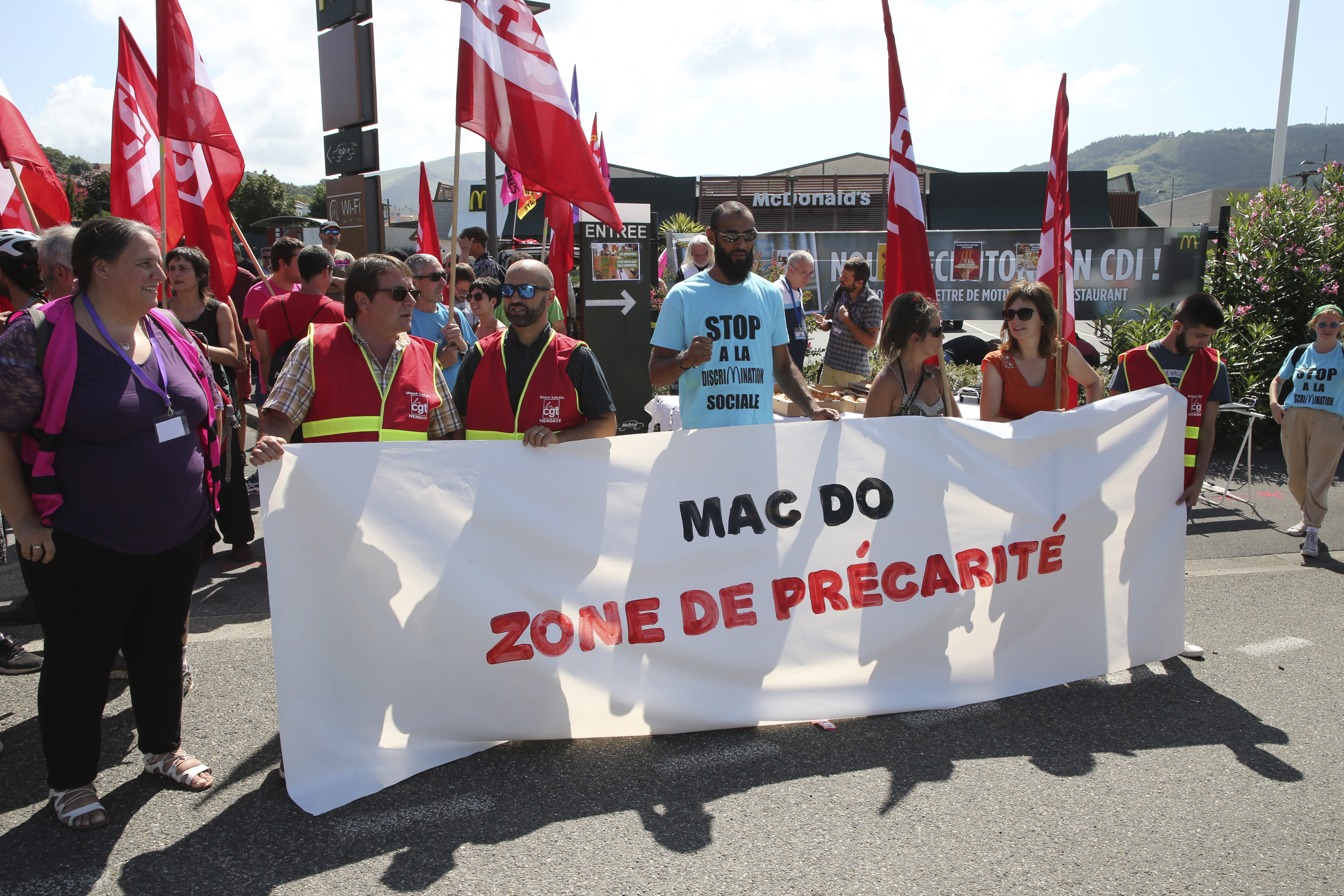 """Unionists demonstrate with a banner reading """"Mac Do, social insecurity zone"""" in front of a McDonald's restaurant, Thursday, Aug. 22, 2019 in Hendaye, southwestern France. The G-7 summit has for the first time co-opted the message of its protesters: Capitalism has led to damaging inequality, hurting the environment also harms the global economy, and a handful of rich countries can't be the only ones making decisions for the world. (AP Photo/Bob Edme)"""