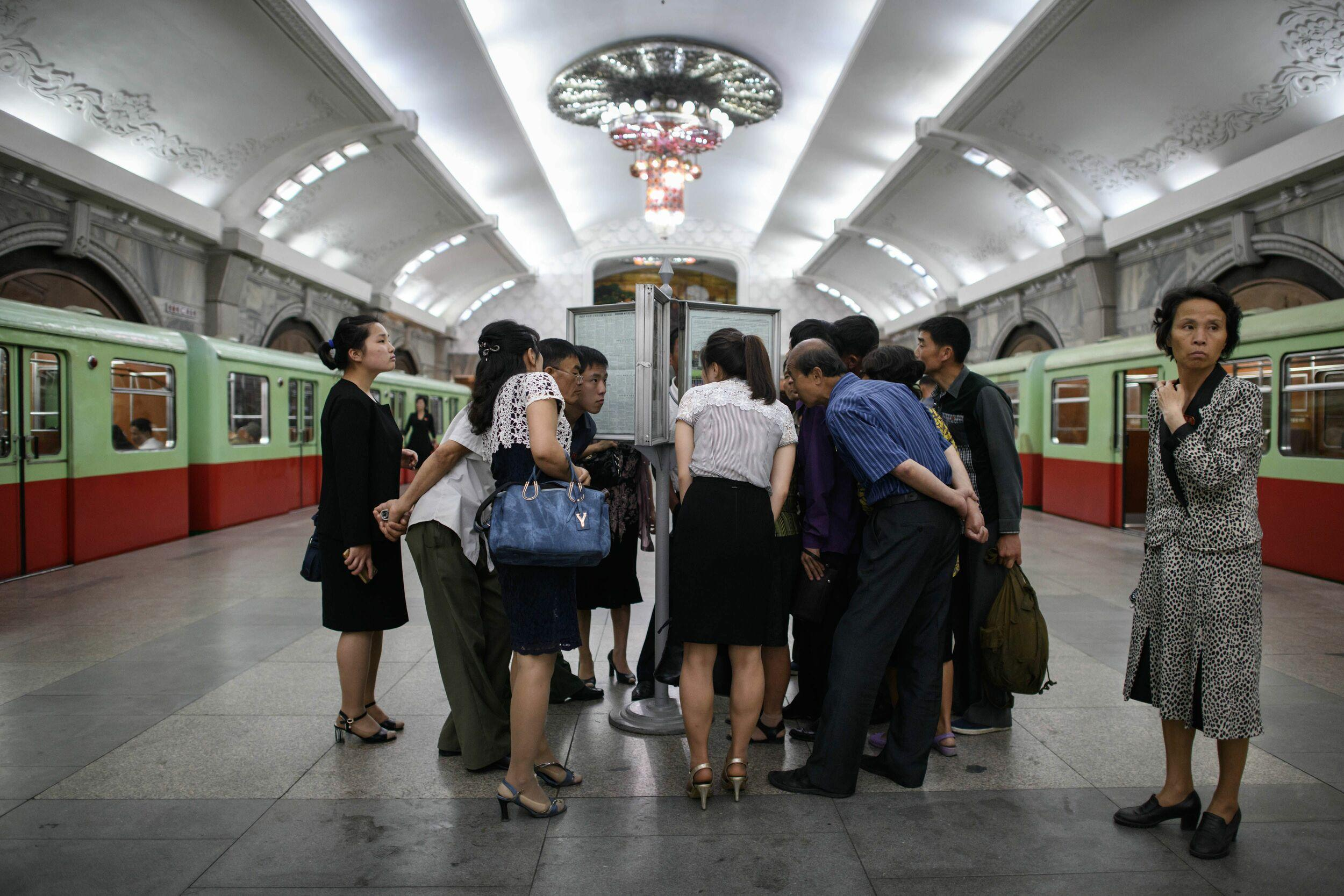 TOPSHOT - Commuters read the latest edition of the Rodong Sinmun newspaper showing images of North Korean leader Kim Jong Un meeting with US president Donald Trump during their summit in Singapore, at a news stand on a subway platform of the Pyongyang metro on June 13, 2018. - Donald Trump accepted an invitation from Kim Jong Un to visit North Korea during their historic summit, Pyongyang state media reported on June 13, as the US president said the world had jumped back from the brink of 'nuclear catastrophe'. (Photo by Ed JONES / AFP)        (Photo credit should read ED JONES/AFP/Getty Images)
