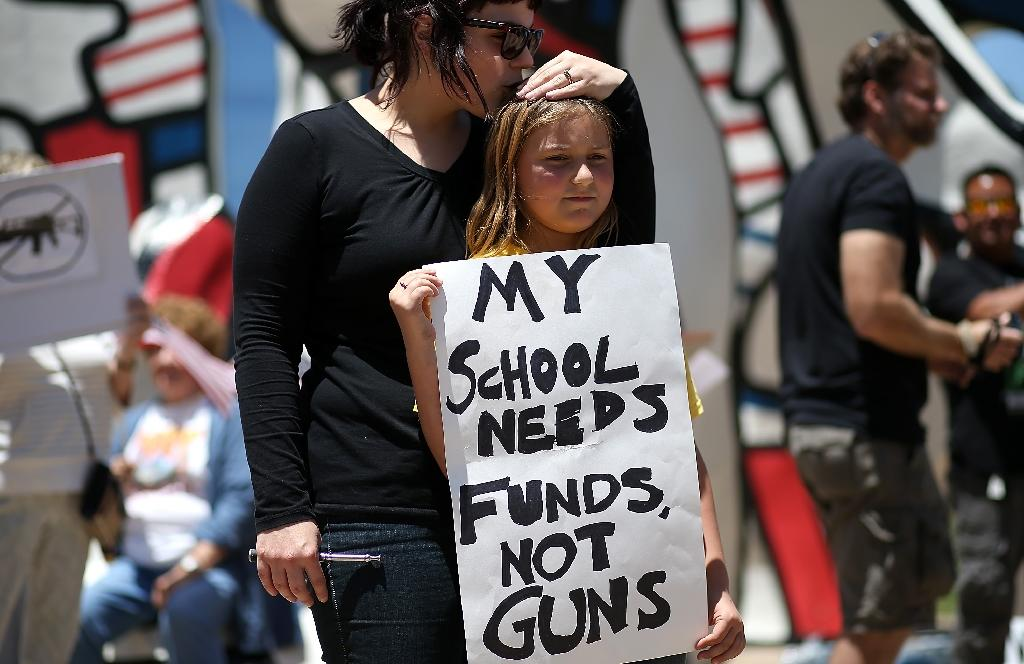 A young protestor is kissed by her mother as she demonstrates in favor of gun regulation outside of a National Rifle Association meeting in 2013 (AFP Photo/Justin Sullivan)