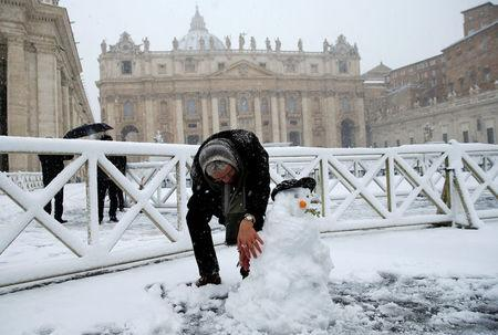 A man makes a snowman during a heavy snowfall in Saint Peter's Square at the Vatican. REUTERS/Max Rossi