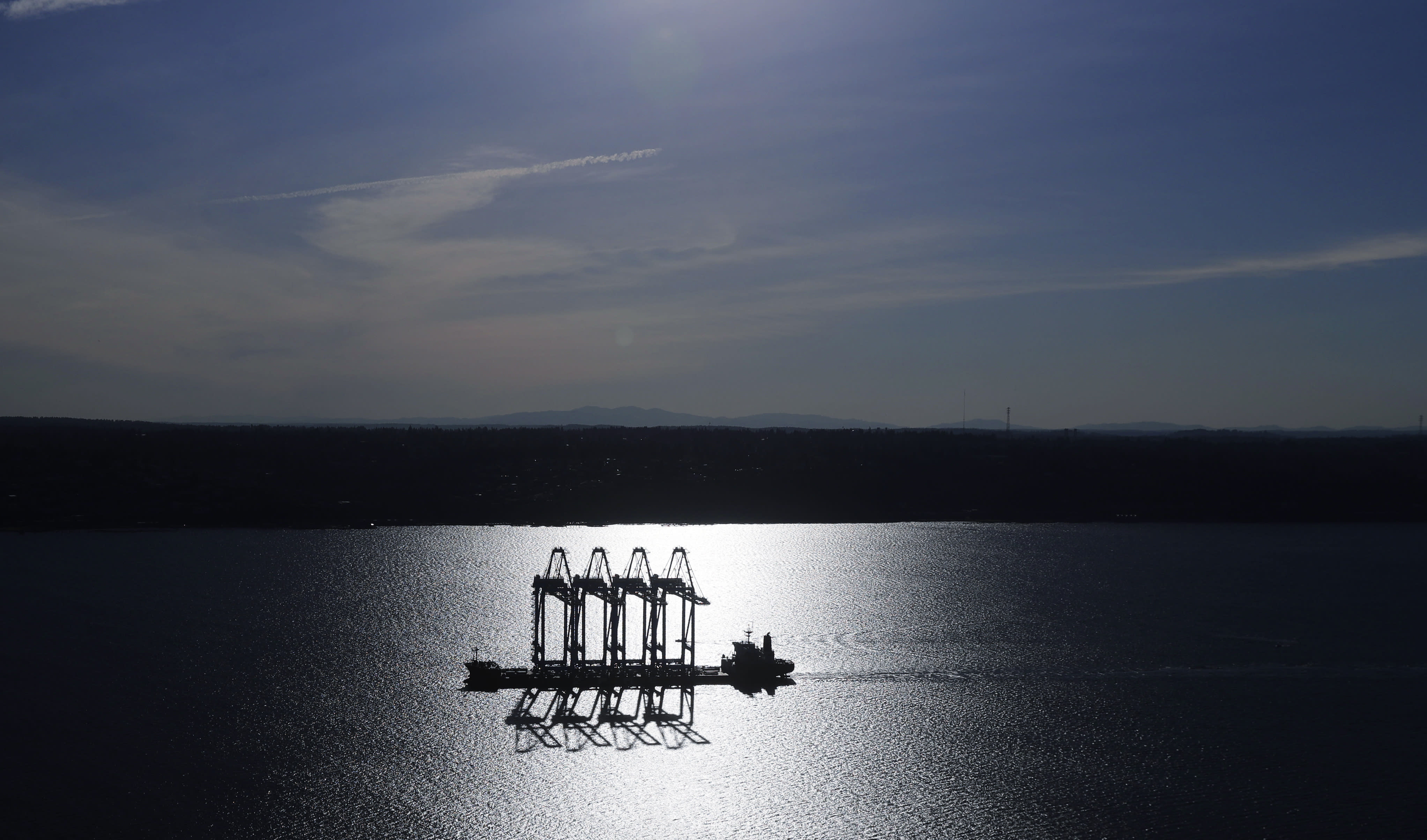 FILE - In this March 5, 2019, file photo the Zhen Hua 31 heavy-lift ship carrying four super-post-Panamax container cranes is silhouetted by the sun as it sails into Commencement Bay in Tacoma, Wash. Most economists were already worried that the odds of a recession are rising, and most of the worries stem from the U.S.-China trade war. (AP Photo/Ted S. Warren, File)