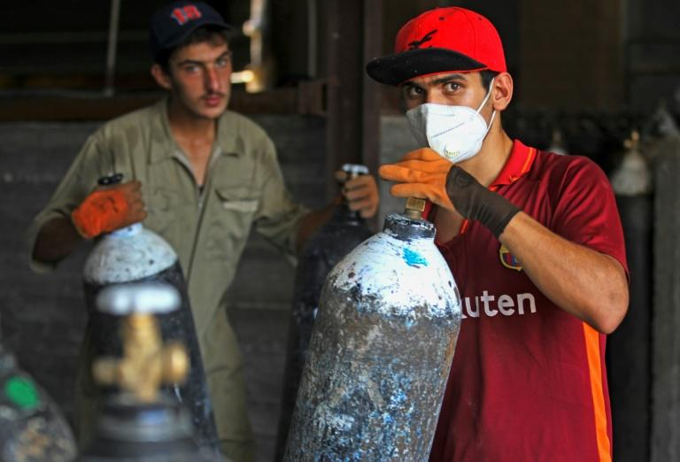 Mask-clad workers move refilled oxygen cylinders at a factory in Taji, north of Iraq's capital Baghdad, before delivering them to hospitals amid the COVID-19 pandemic