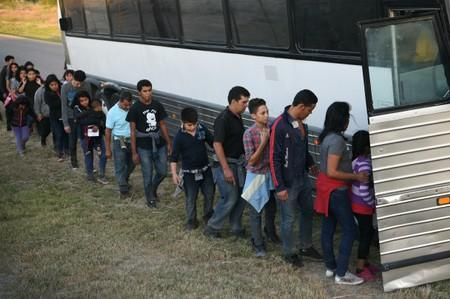 Migrants board a transport bus after turning themselves in to law enforcement to seek asylum following an illegal crossing of the Rio Grande near Penitas