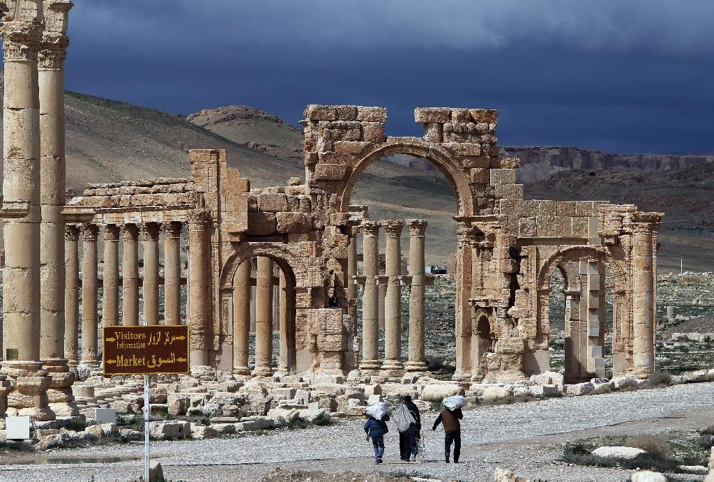 A picture taken on March 14, 2014 shows visitors walking near the famous Arch of Triumph of the ancient oasis city of Palmyra. Islamic State extremists have blown up the famous arch and other monuments at the UNESCO World Heritage Site