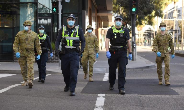 A group of police and soldiers patrol the Docklands area of Melbourne after the announcement of new restrictions to curb the spread of the coronavirus (AFP Photo/William WEST)