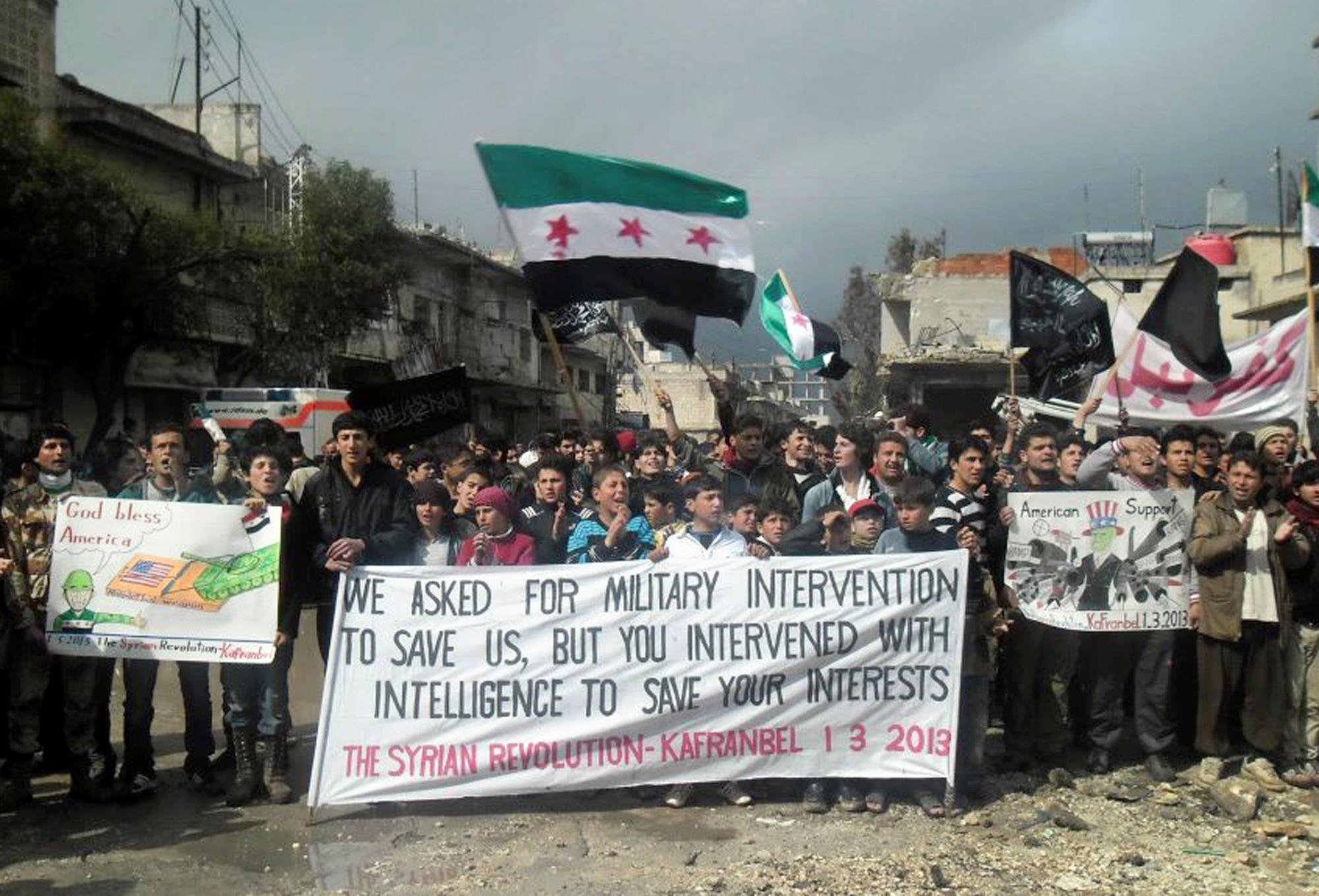 This citizen journalism image provided by Edlib News Network, ENN, which has been authenticated based on its contents and other AP reporting, shows anti-Syrian regime protesters holding a banner and Syrian revolution flags, during a demonstration, at Kafr Nabil town, in Idlib province, northern Syria, Friday, March. 1, 2013. Syrian government forces fought fierce clashes with rebels attacking a police academy near the northern city of Aleppo on Friday, while the bodies of 10 men most of them shot in the head were found dumped along the side of a road outside Damascus, activists said. (AP Photo/Edlib News Network ENN)